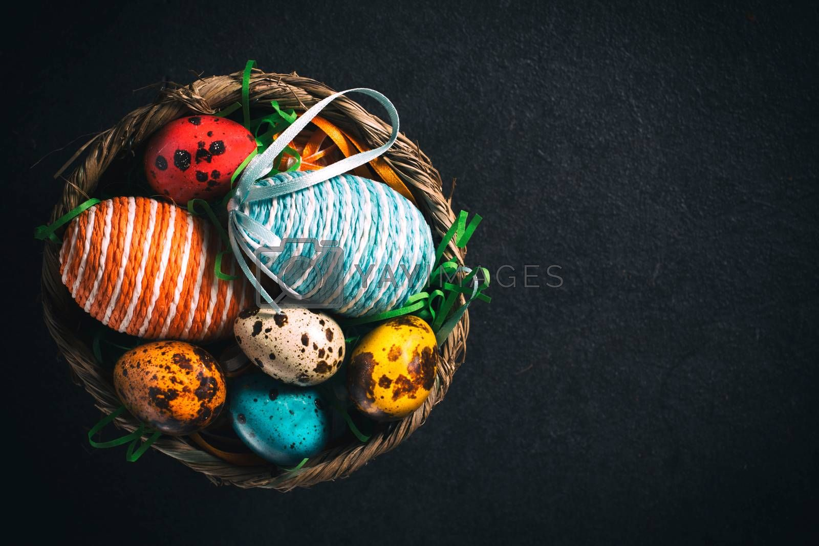 Colorful Easter eggs from above on dark background with blank space