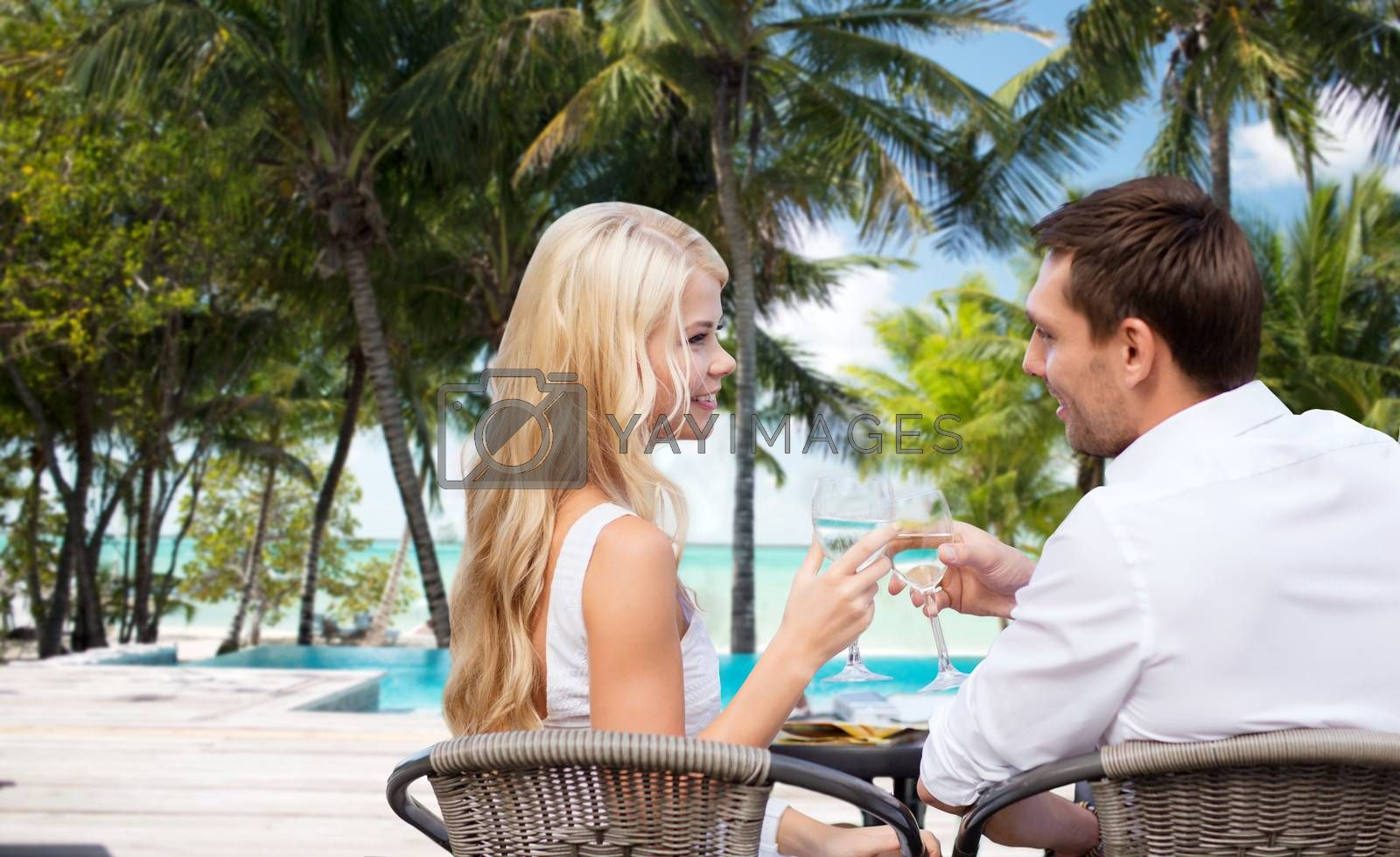 summer holidays, travel, tourism, celebration and dating concept - happy couple drinking wine in cafe over hotel beach with swimming pool background