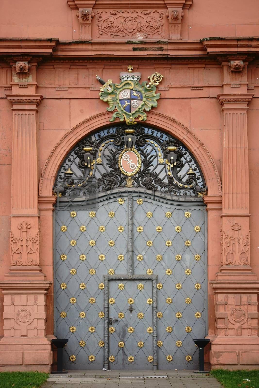Mainz, Germany - September 19, 2015: The entrance door of the Electoral Palace Mainz studded with gold, iron ornaments and a coat of arms on September 19, 2015 in Mainz.