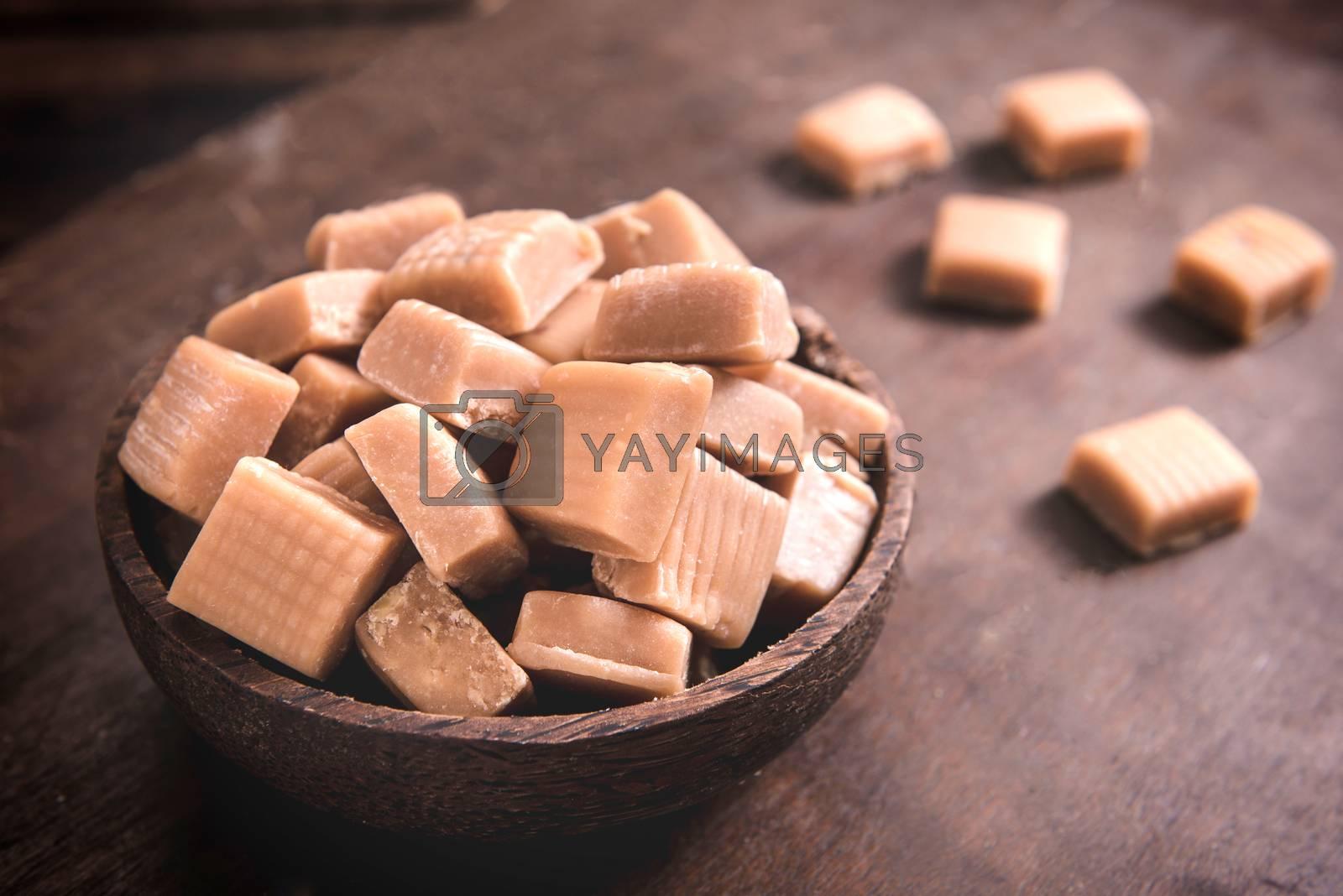 Milk and caramel handmade bonbons on wooden background,