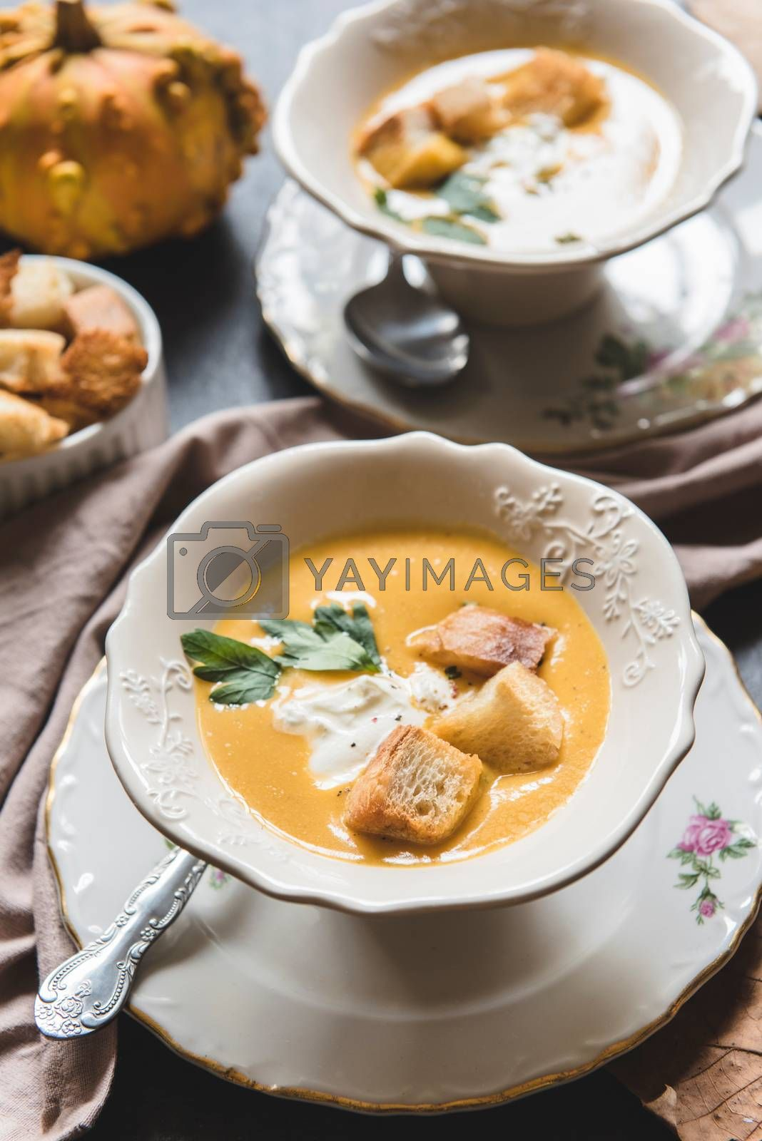 Homemade pumpkin soup with milk cream and croutons bread in bowl, selective focus