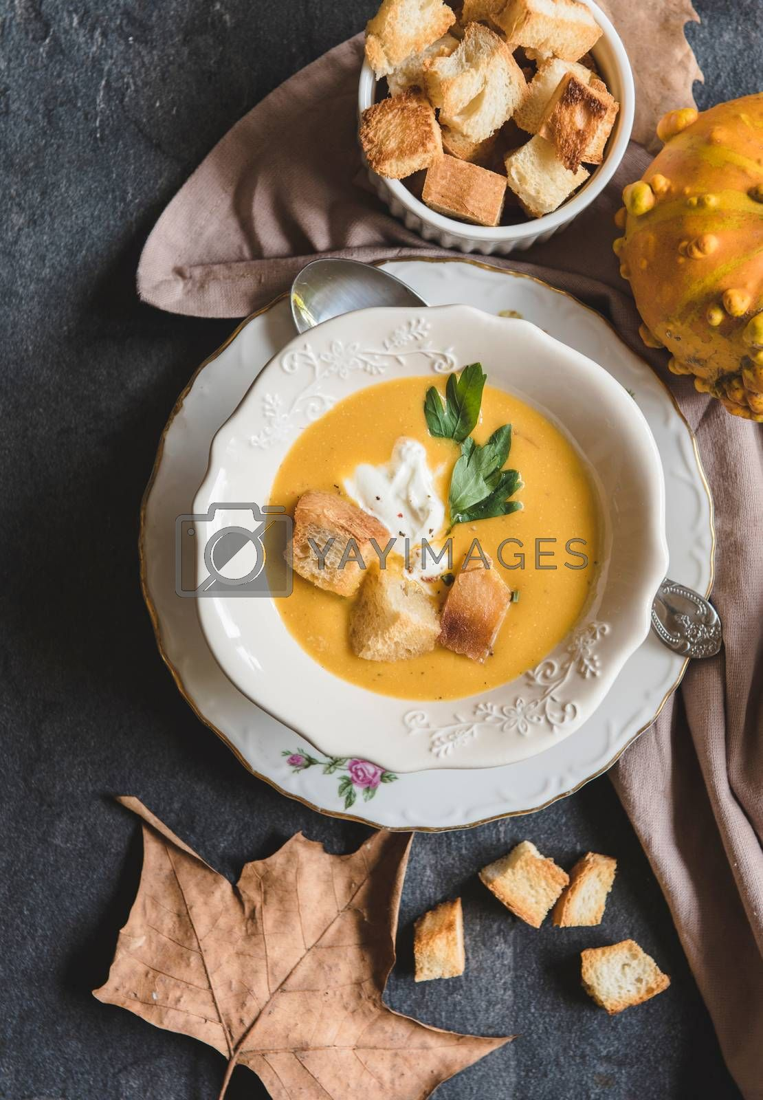 Homemade pumpkin soup with milk cream and croutons bread in bowl, from above
