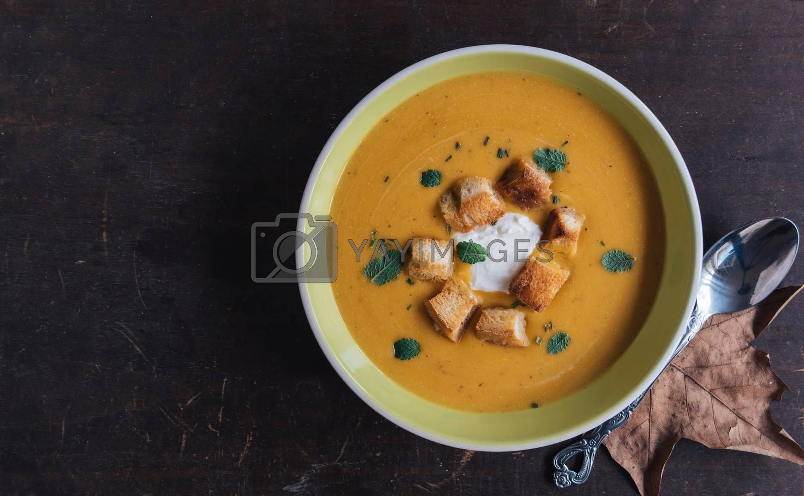 Served homemade pumpkin soup with milk cream and croutons bread in plate on wooden background with blank space