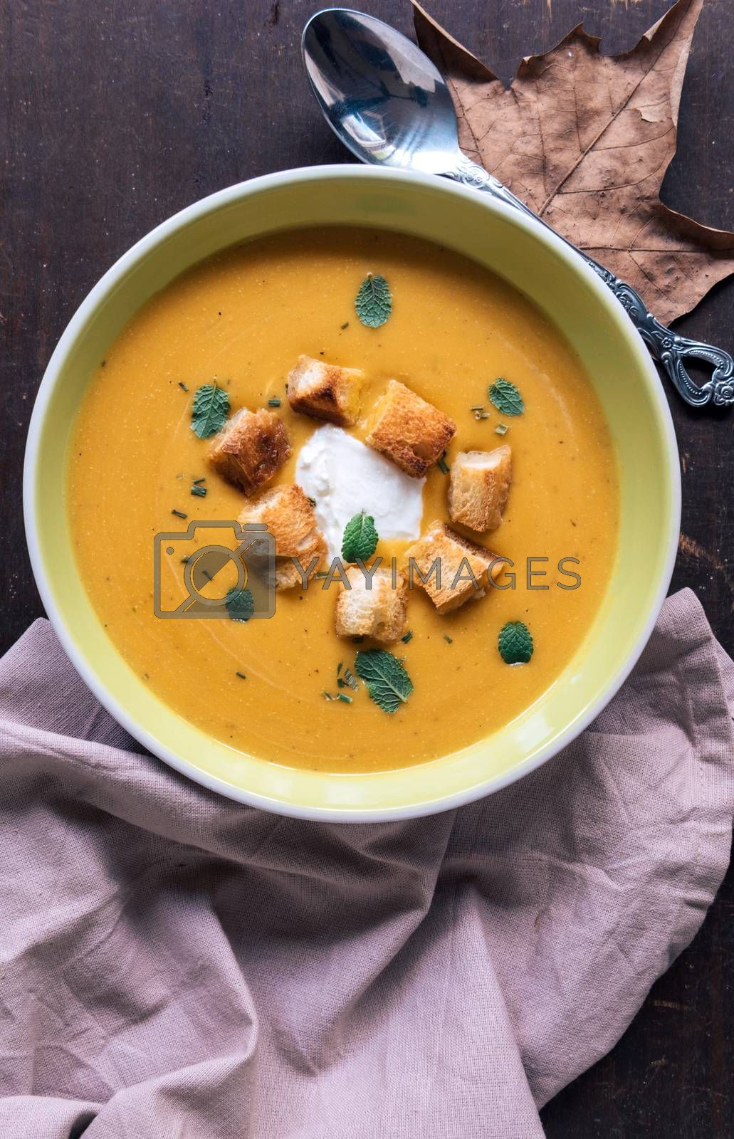 Served homemade pumpkin soup with milk cream and croutons bread in plate on wooden background