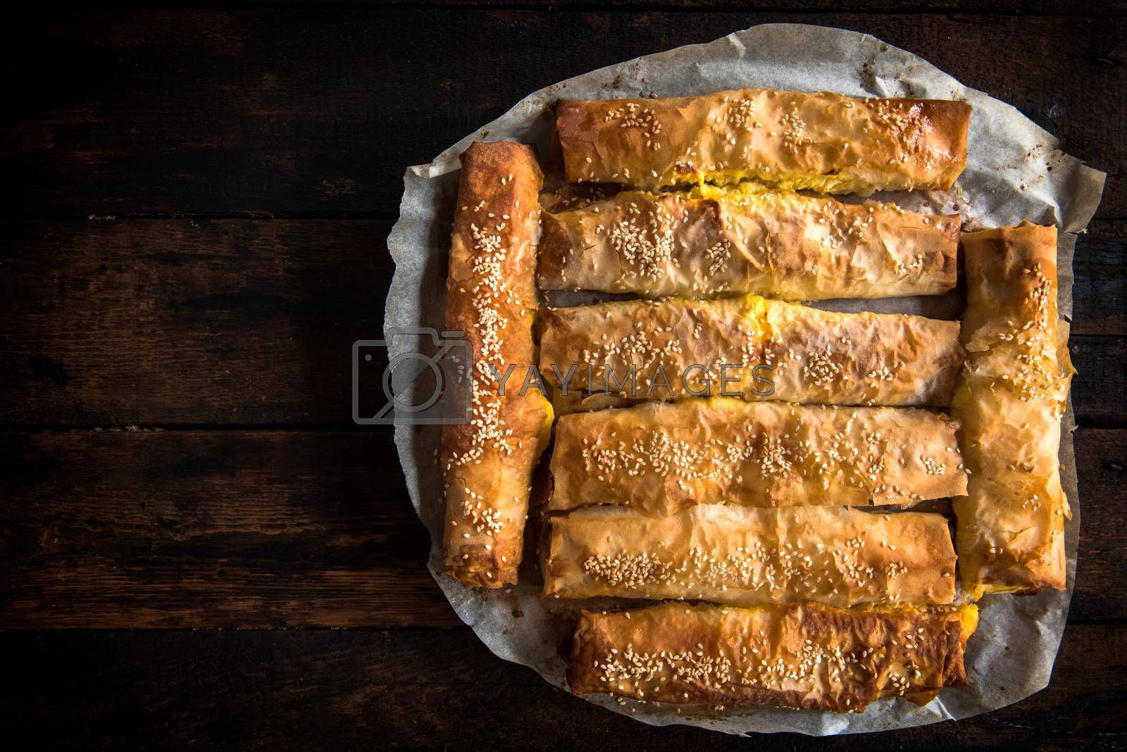 Homemade cheese pie sticks on wooden background with blank space, from above