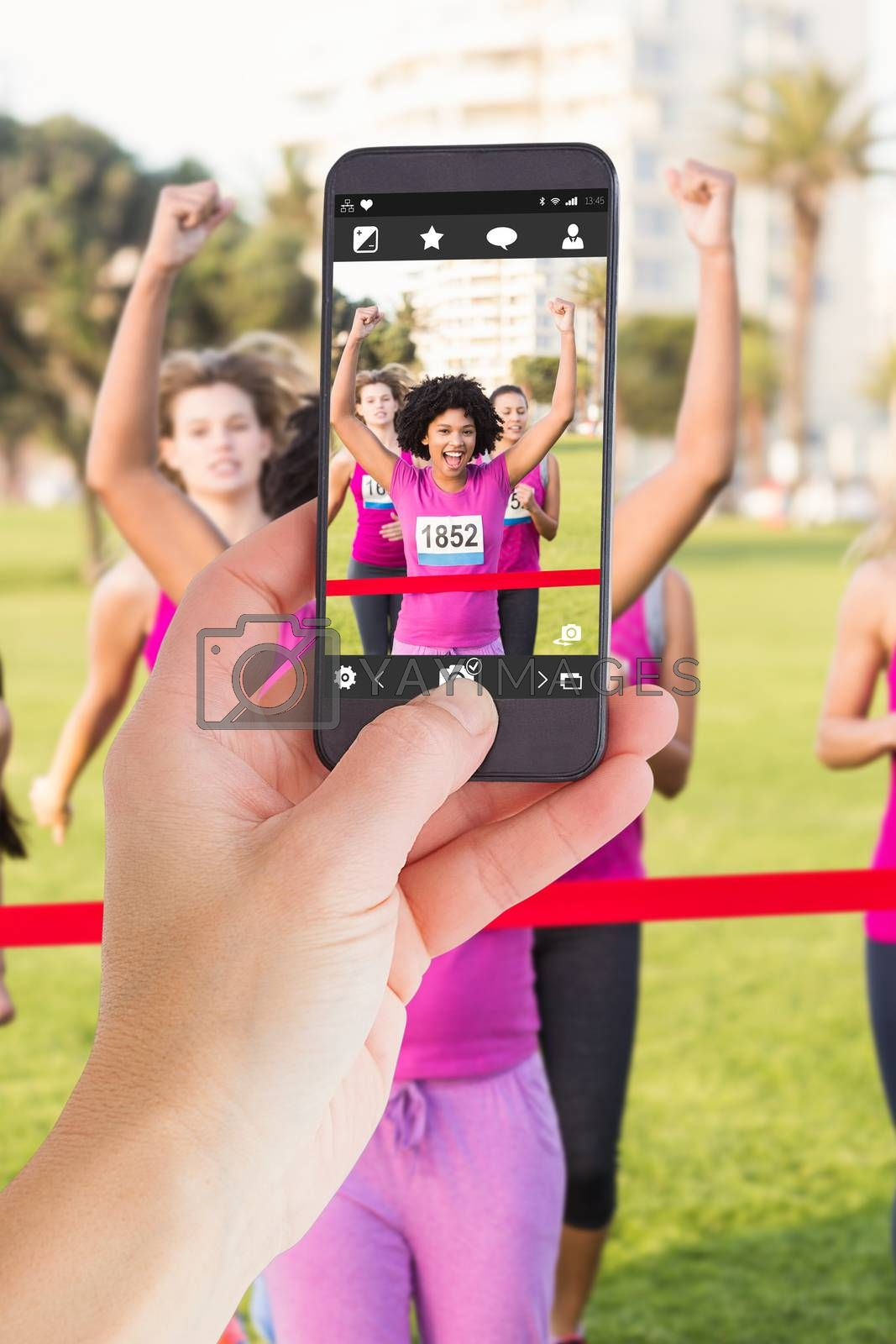 Female hand holding a smartphone against cheering young woman winning breast cancer marathon