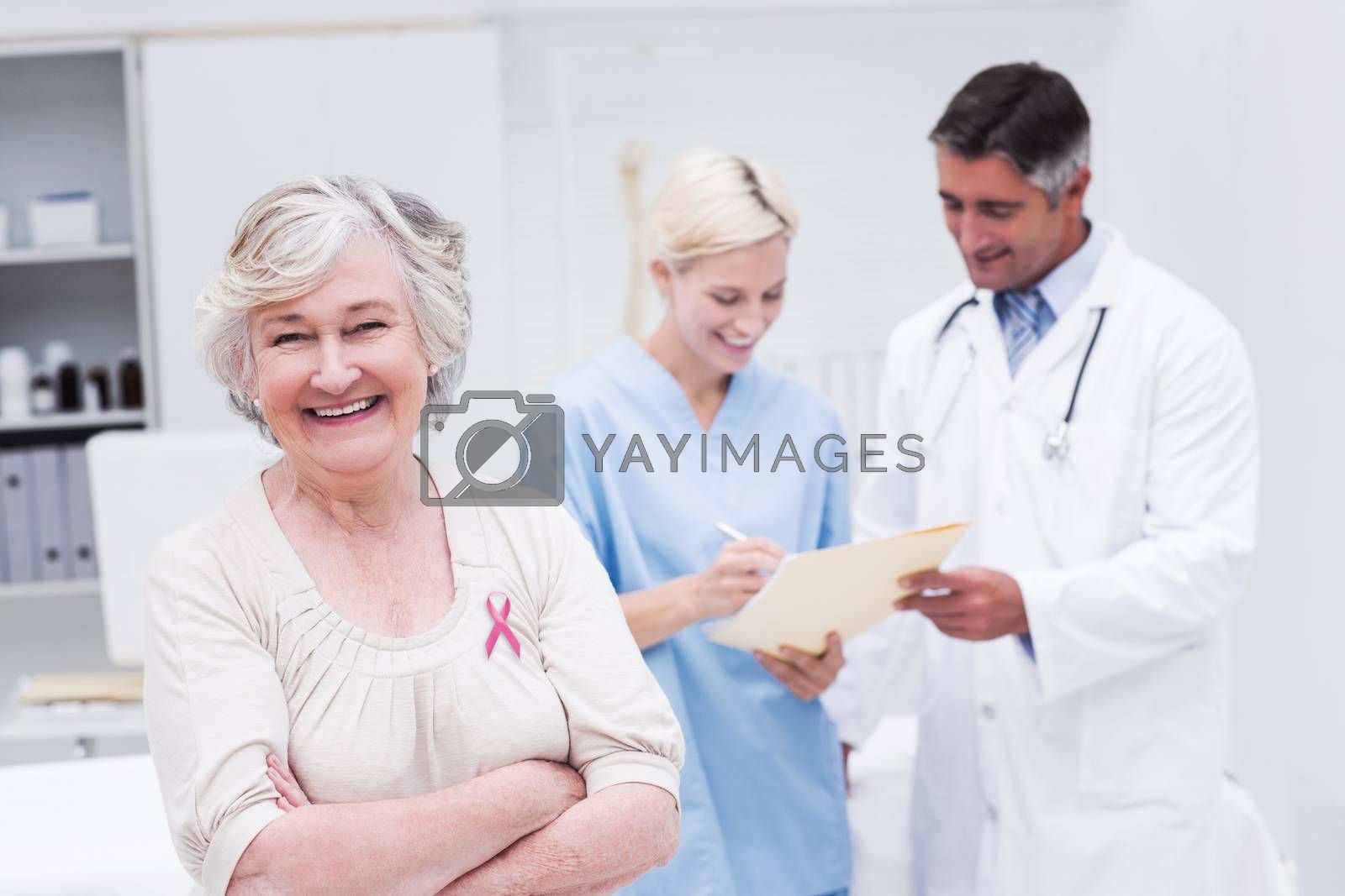 Pink awareness ribbon against patient smiling while doctor and nurse discussing in clinic