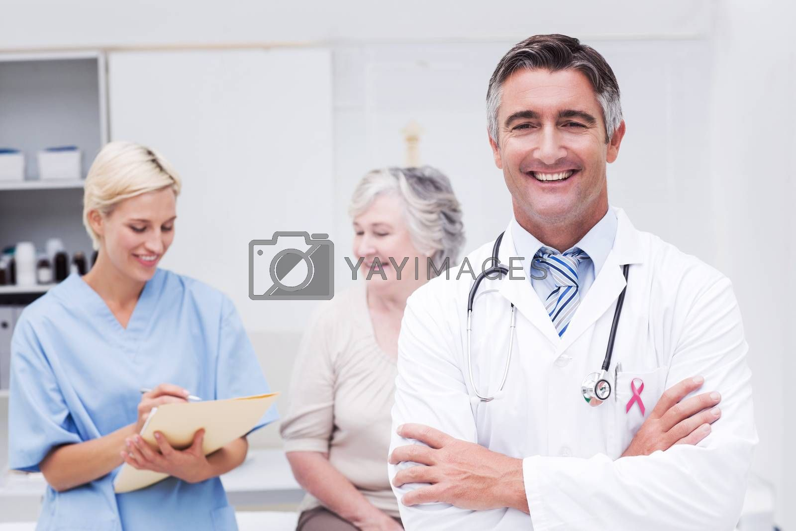 Pink awareness ribbon against doctor standing arms crossed with nurse and patient in background