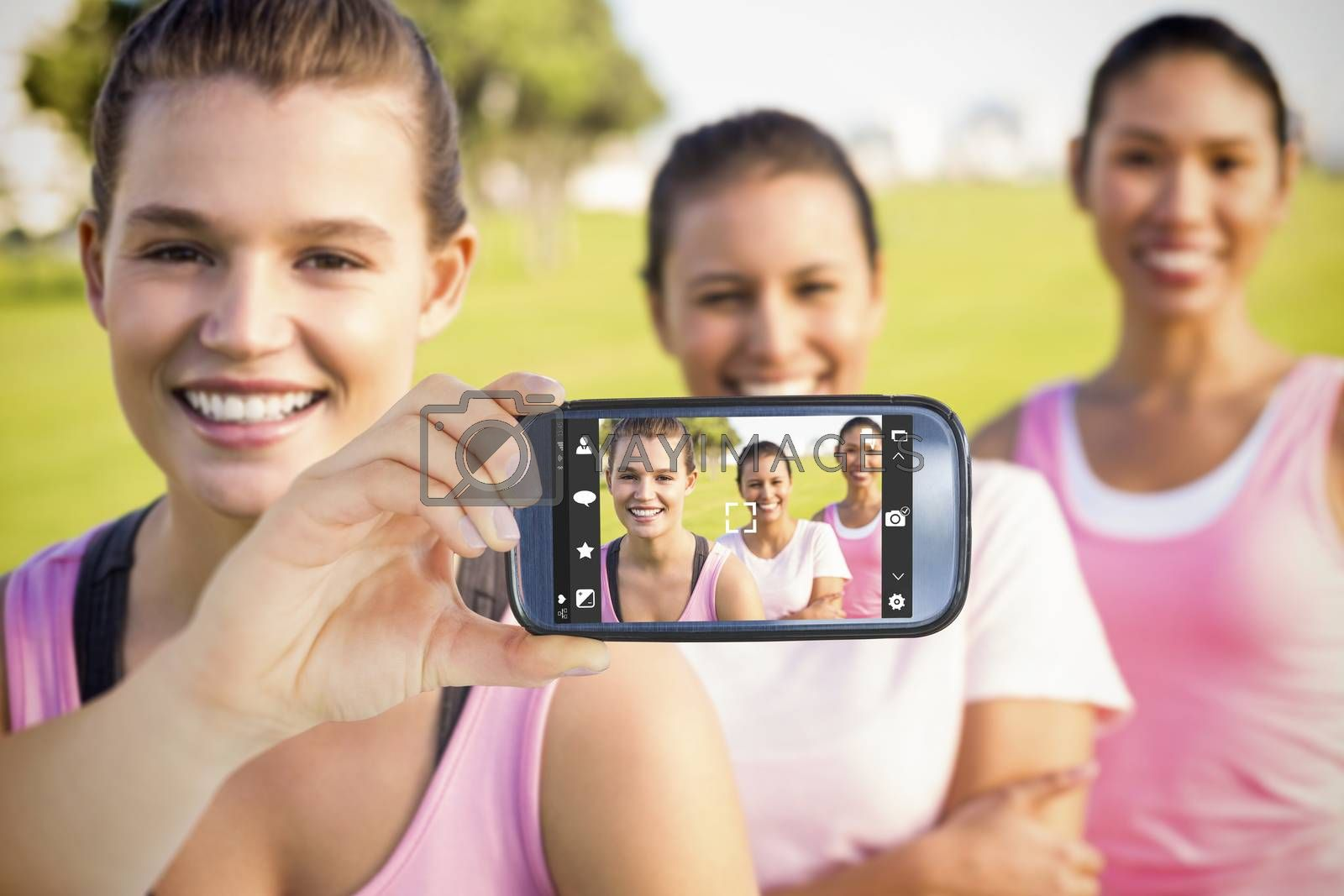 Hand holding smartphone showing against three smiling women wearing pink for breast cancer