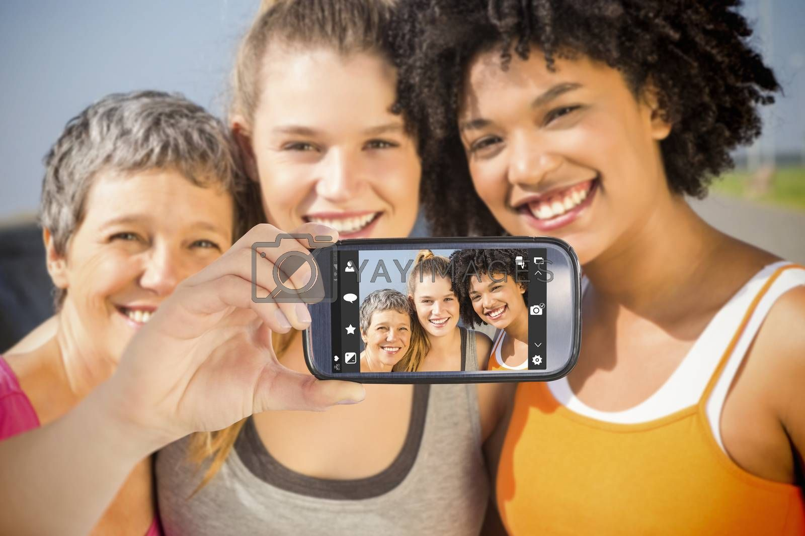 Hand holding smartphone showing against sporty women smiling at camera