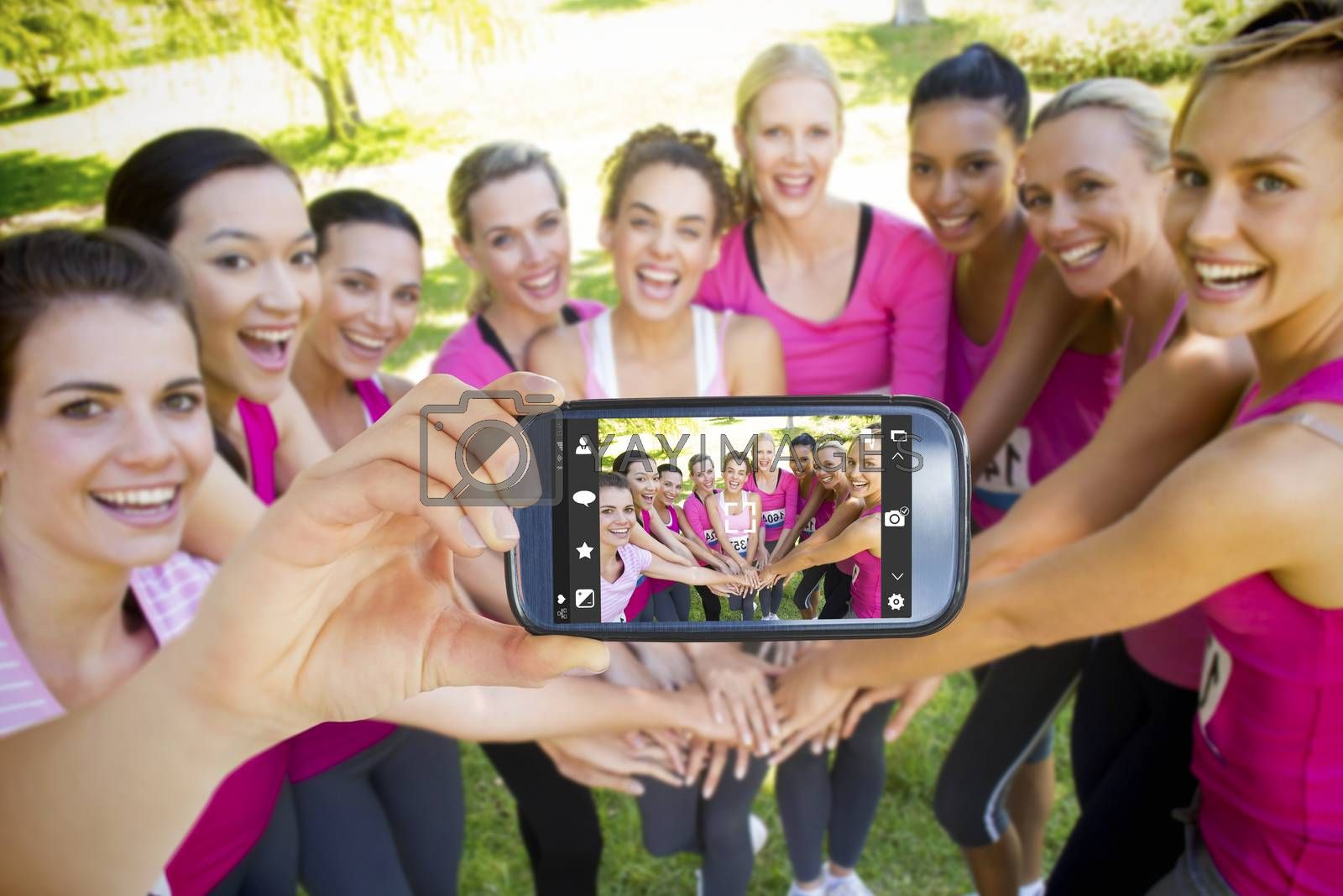 Hand holding smartphone showing against smiling women running for breast cancer awareness