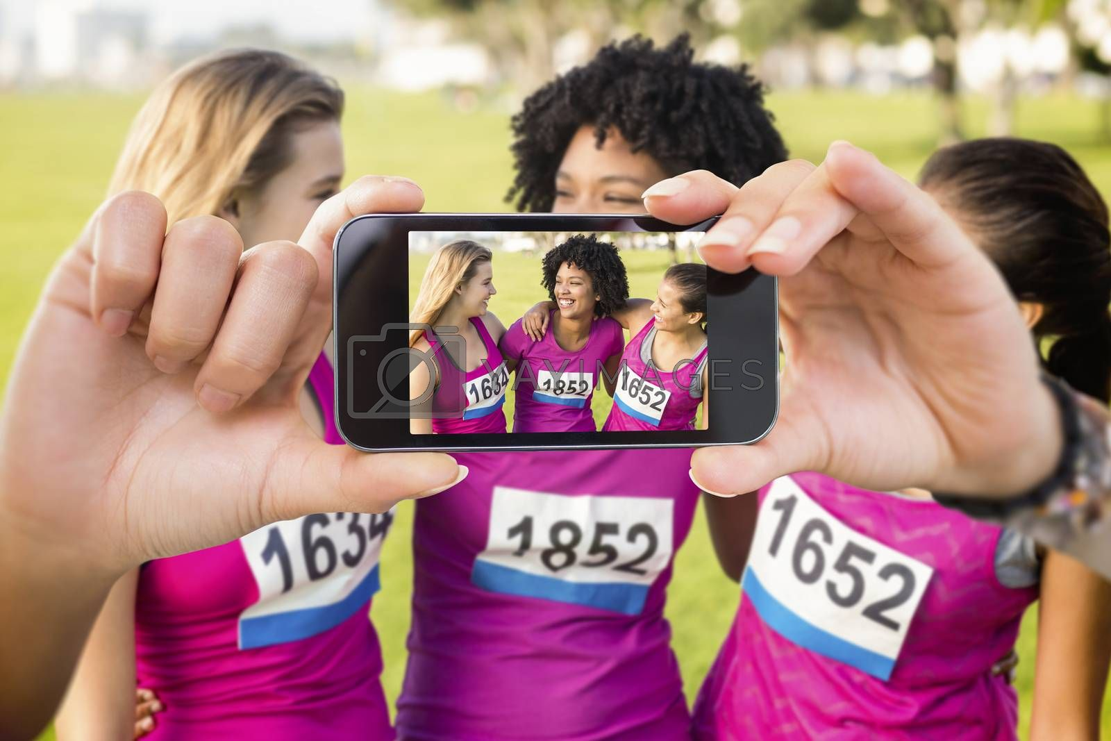 Hand holding smartphone showing against three laughing runners supporting breast cancer marathon