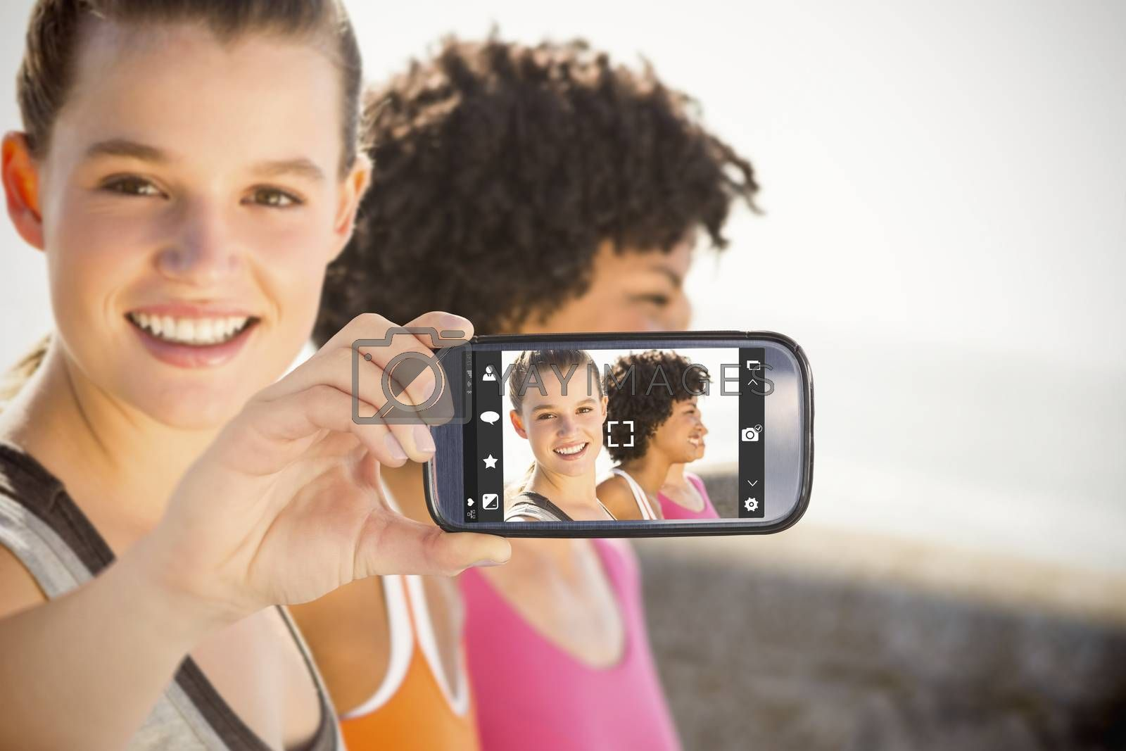 Hand holding smartphone showing against smiling sporty woman with two friends