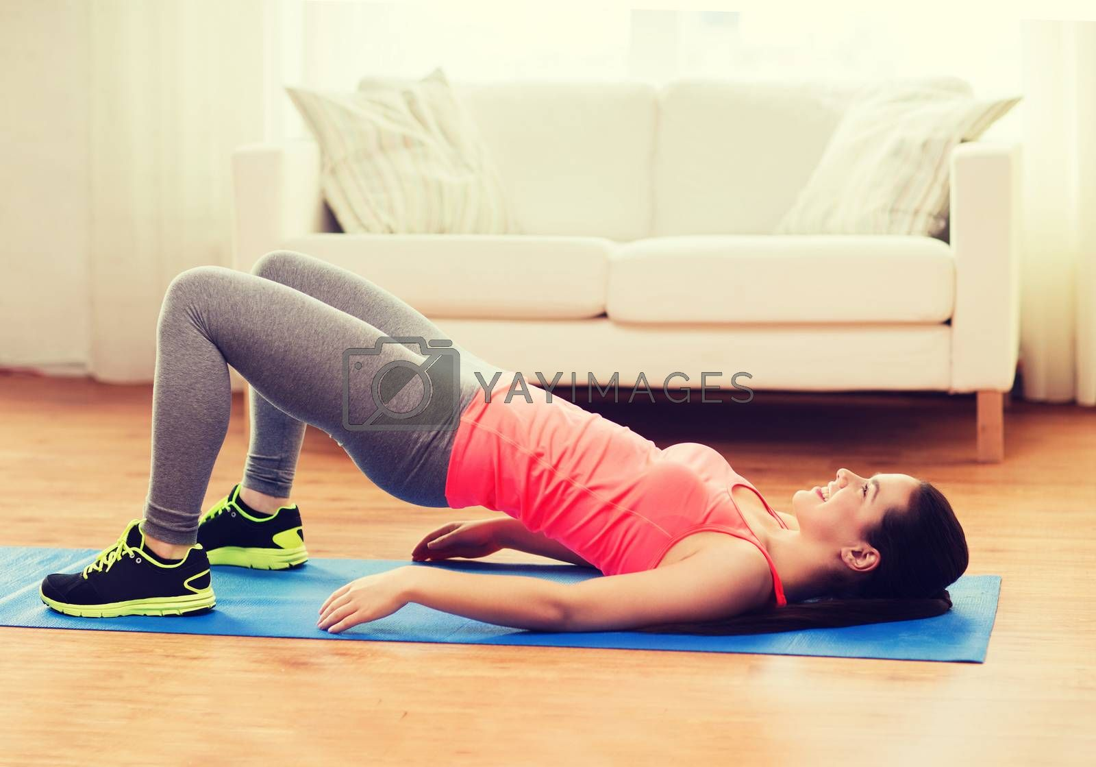 fitness, home and diet concept - smiling teenage girl doing exercise for legs and buttocks on floor at home