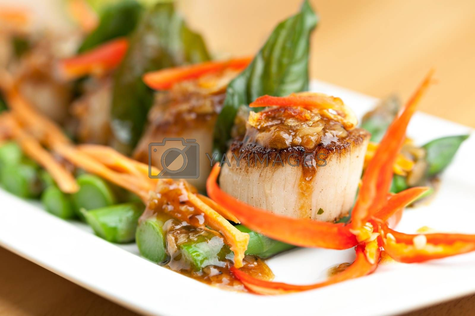 Spicy thai scallops on a bed of asparagus spears.