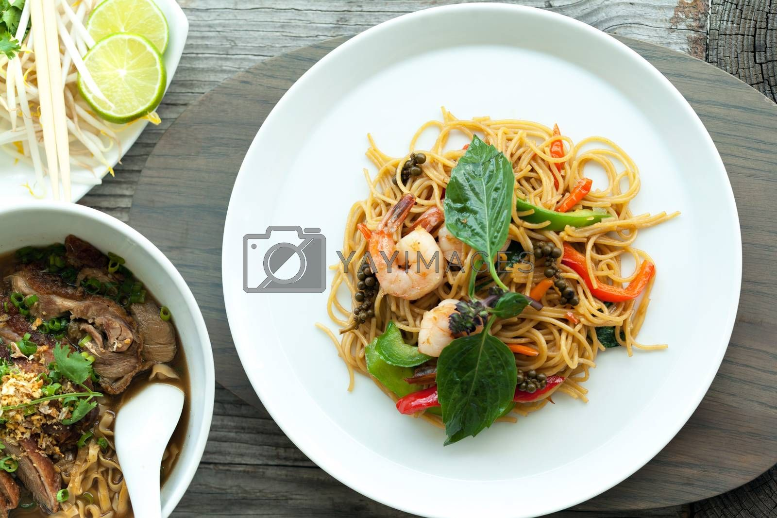 Thai food dishes with shrimp and noodles and soup with duck.