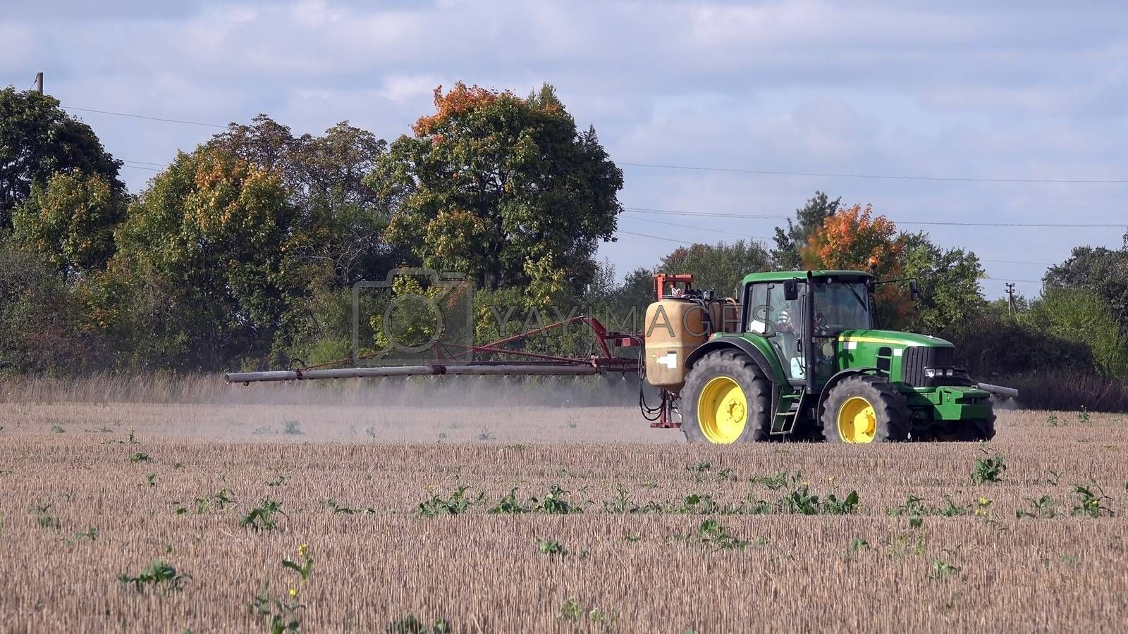 Tractor spraying stubble field with herbicide chemicals in autumn. Farmer with modern vehicle kill weeds in agriculture field before winter.