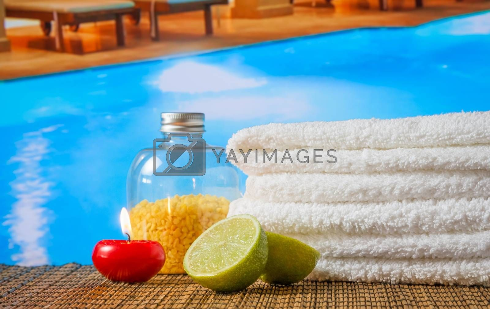 Spa massage border background with towel stacked,red candle and lime near swimming pool by donfiore