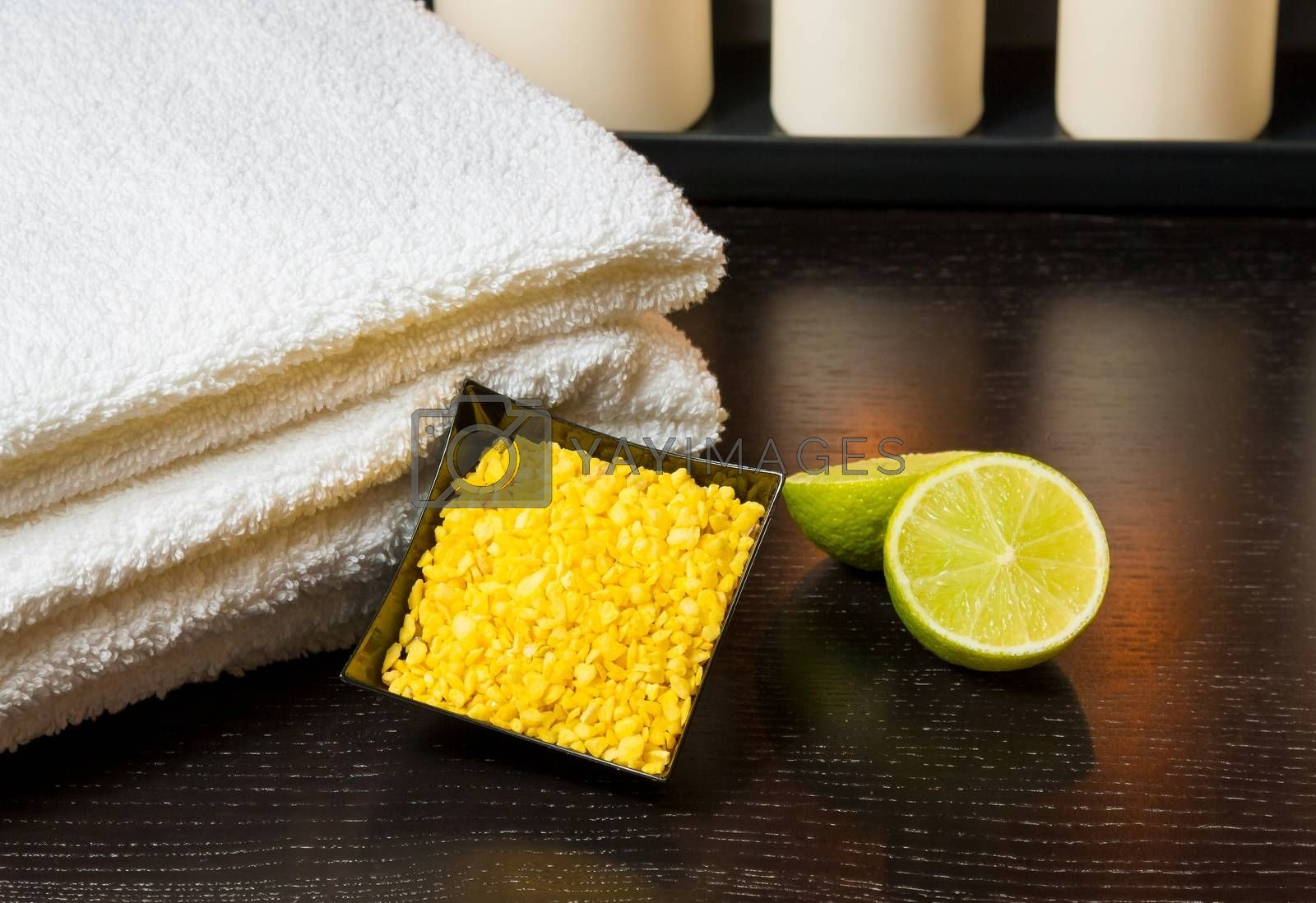 spa massage with towel stacked white candles sea salt and lime by donfiore