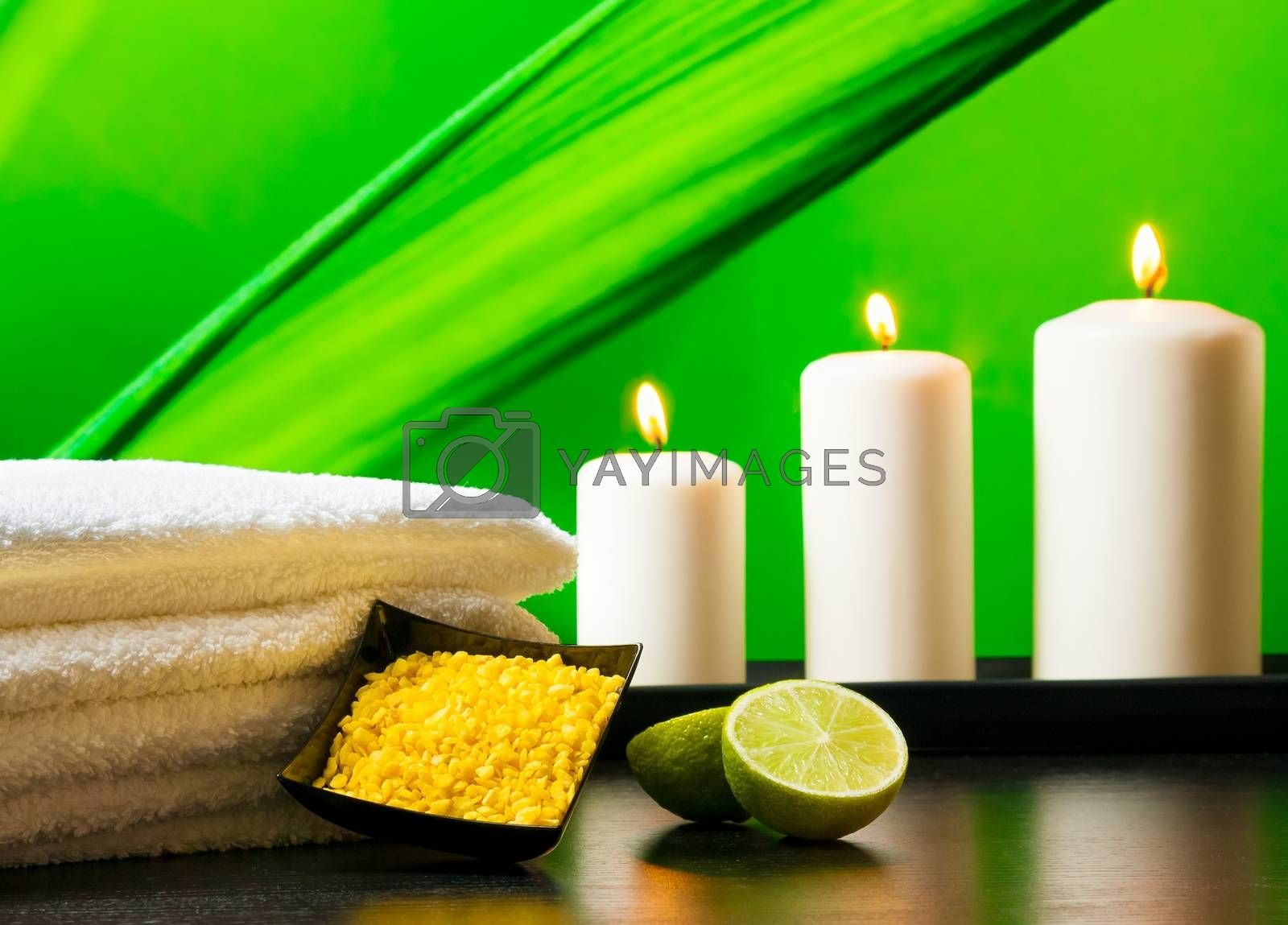 Spa massage border background with towel stacked sea salt candles and lime by donfiore