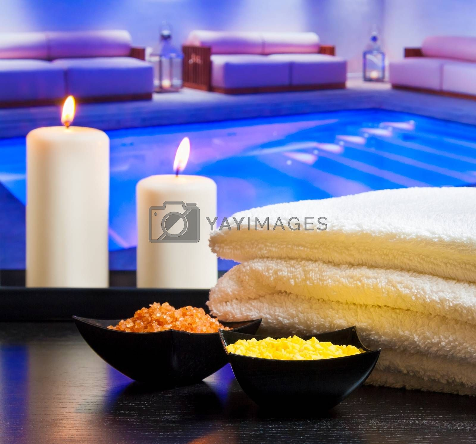 Spa massage border background with towel stacked candles and sea salt near swimming pool by donfiore