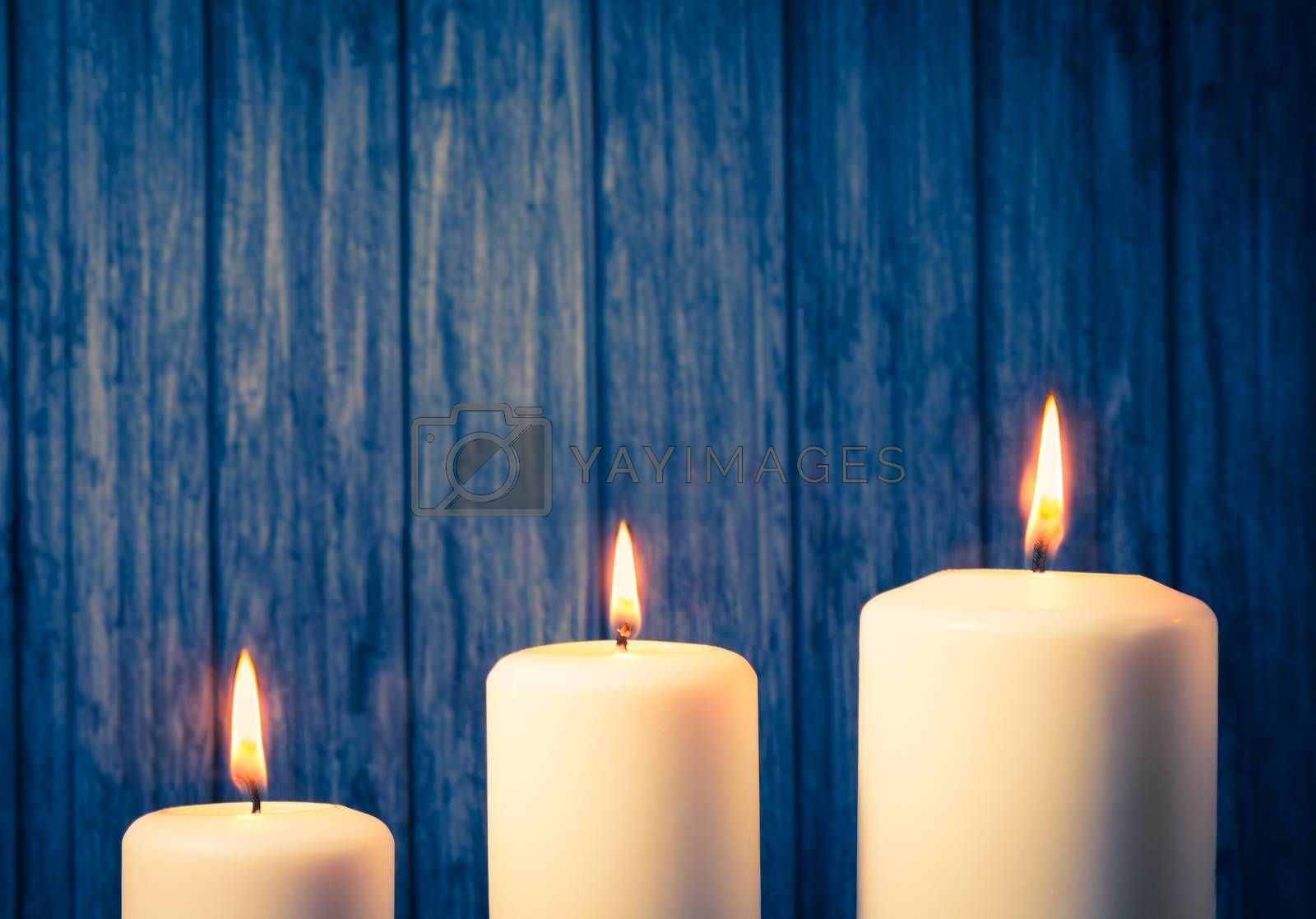 three white candles on warm atmosphere  by donfiore
