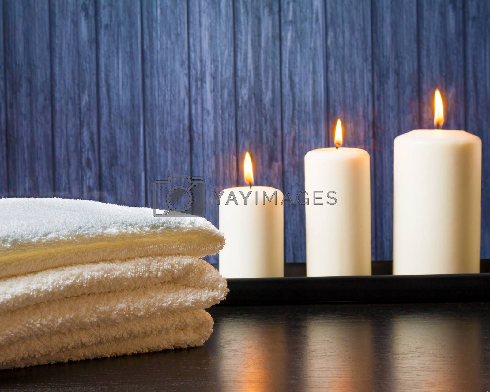 Spa massage border background with towel stacked and candles by donfiore