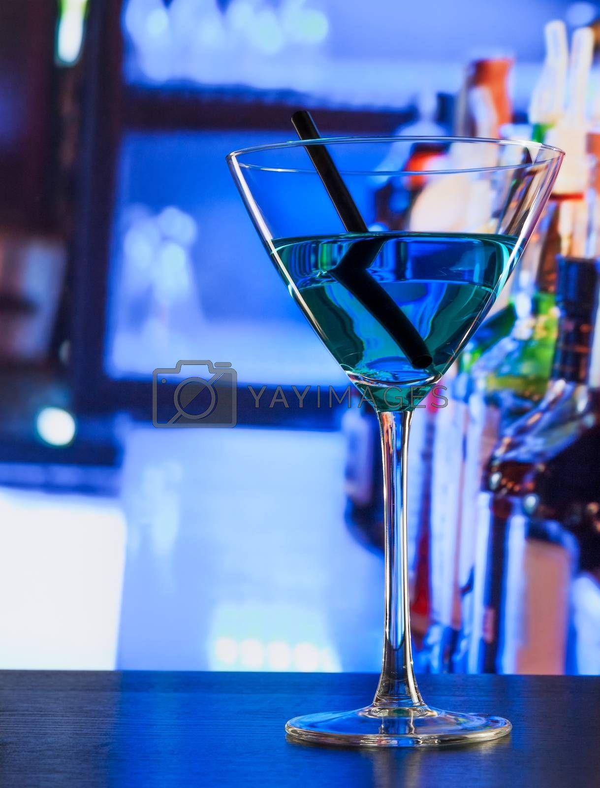 blue cocktail drink on a wood table by donfiore
