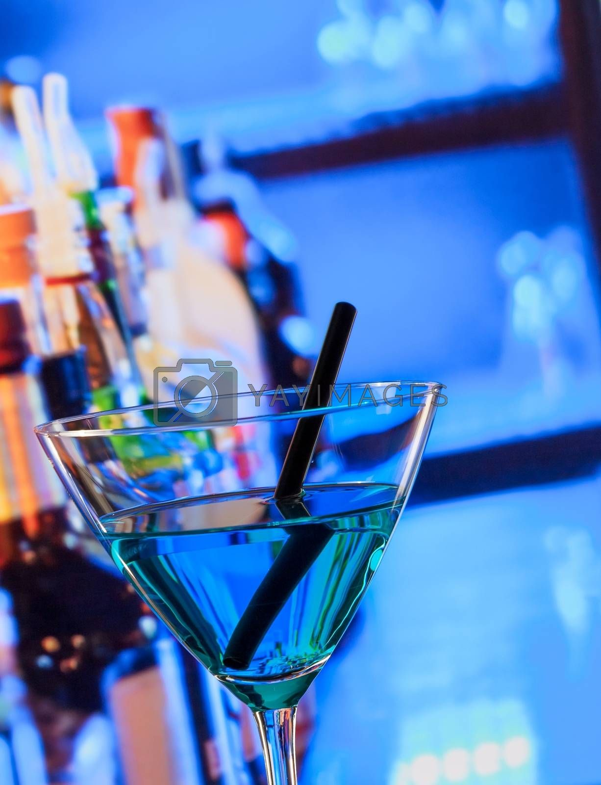 blue cocktail drink on a bar table by donfiore