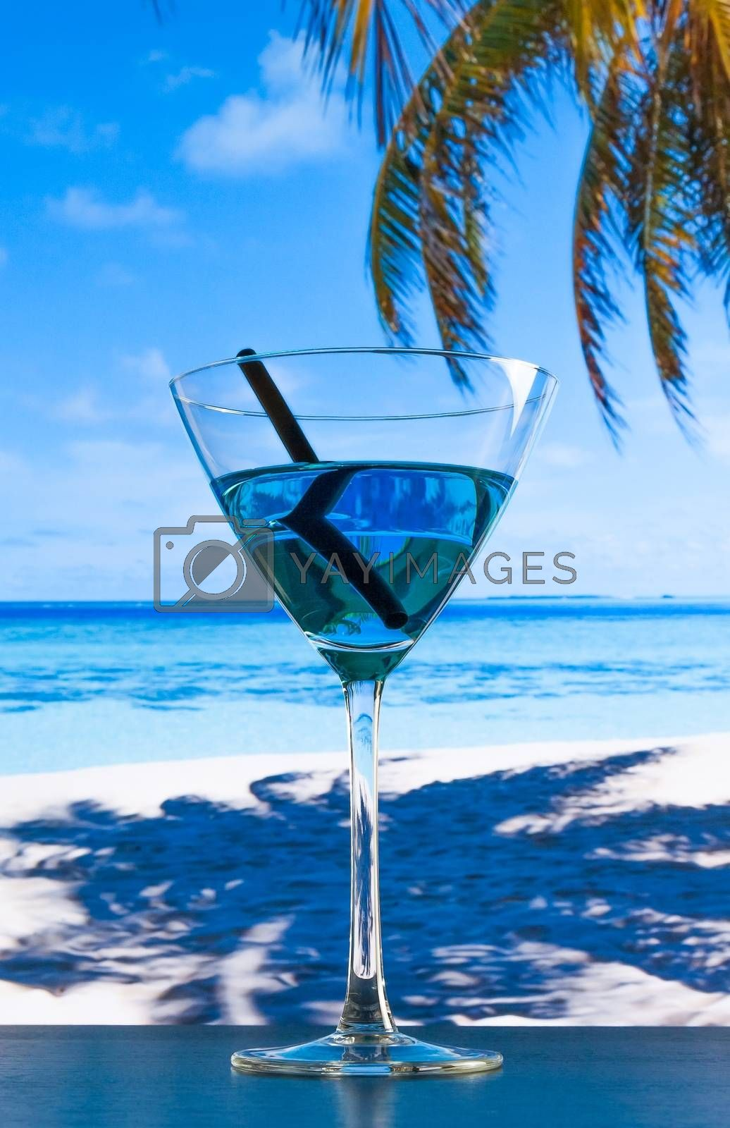 blue cocktail on beach on wood table  by donfiore