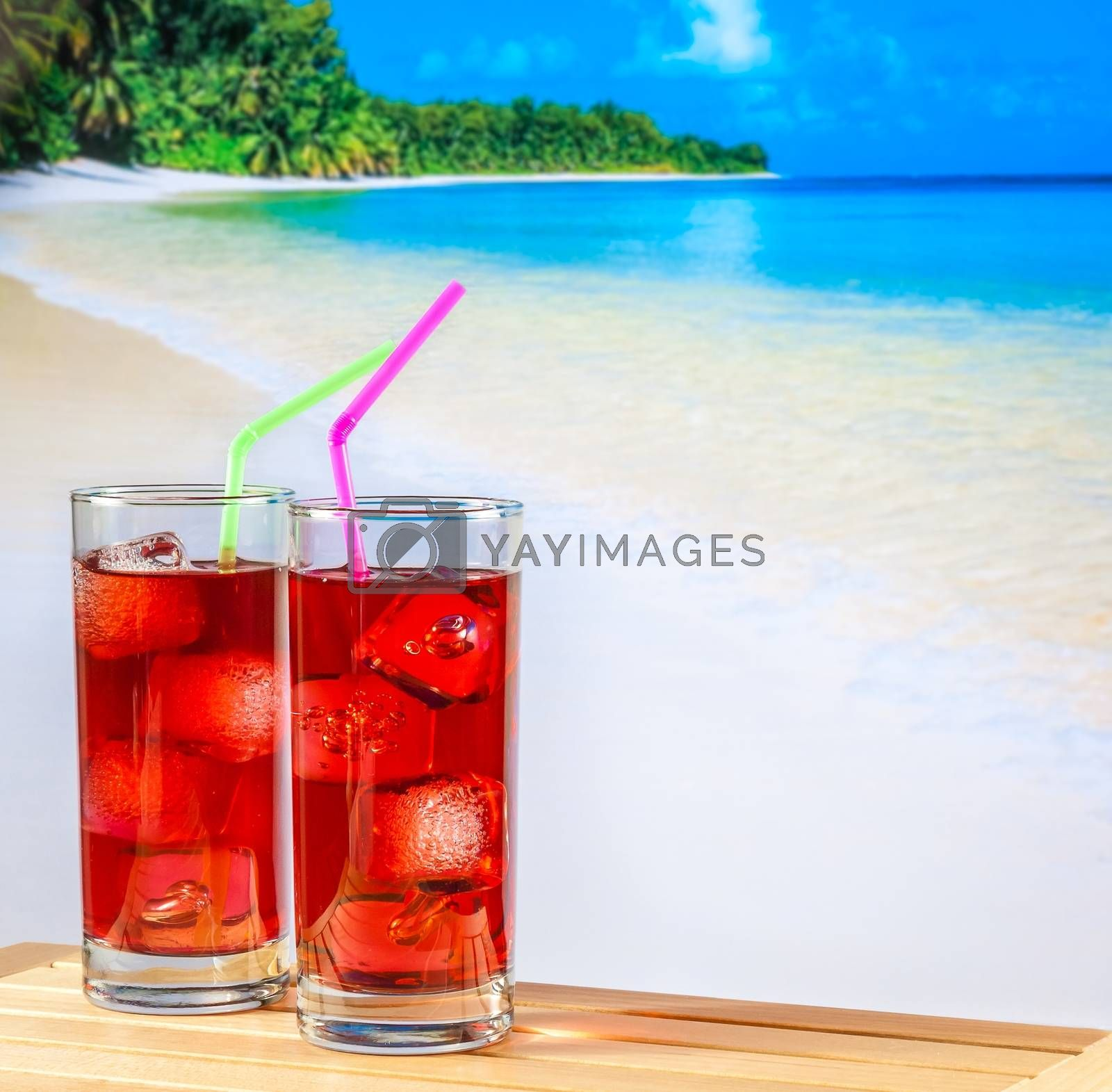 two glasses of red cocktail with blur beach and space for text by donfiore