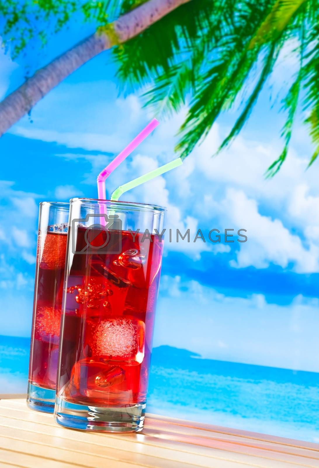 glasses of red cocktail with blur beach and palm by donfiore