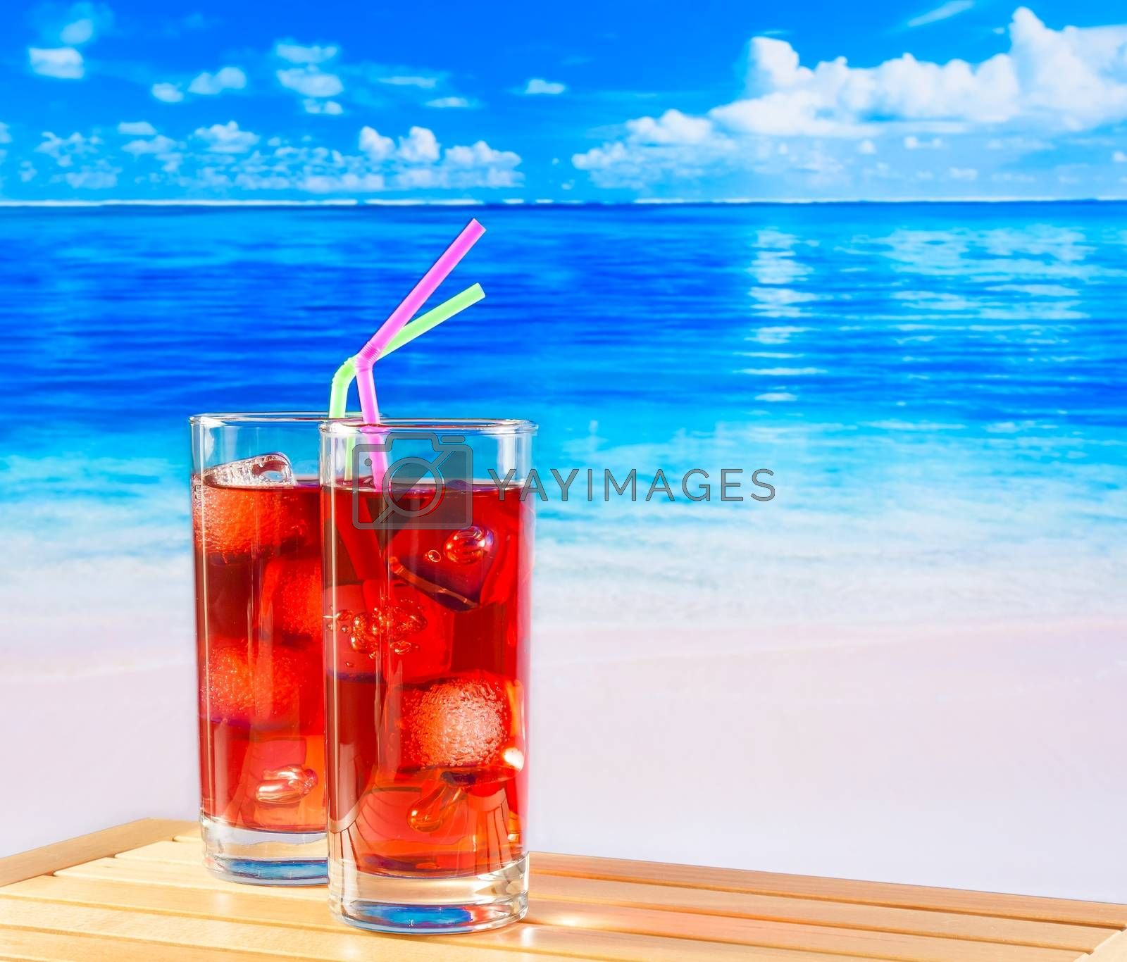 glasses of red cocktail with blur beach by donfiore