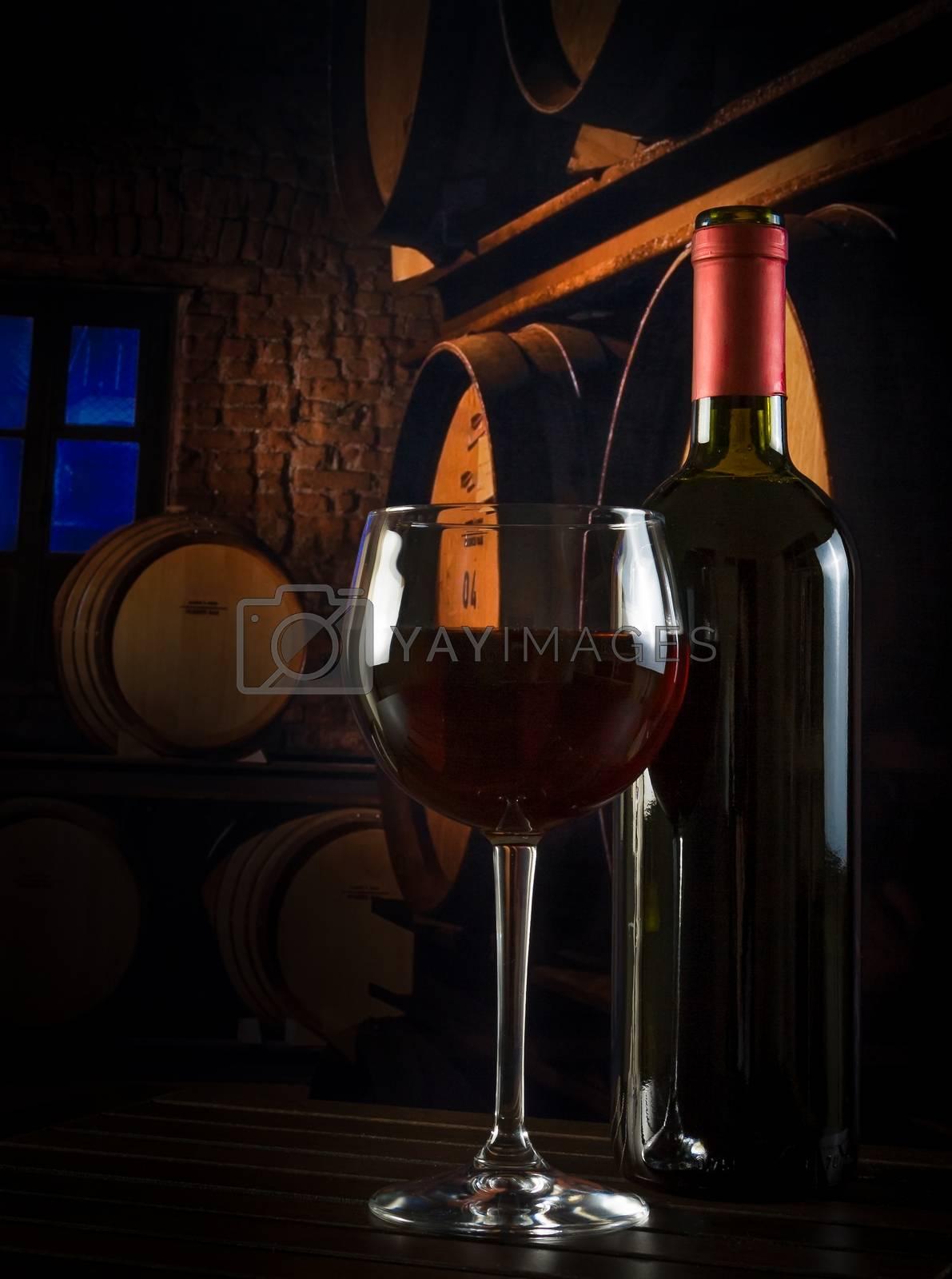 wine glass near bottle in old wine cellar by donfiore