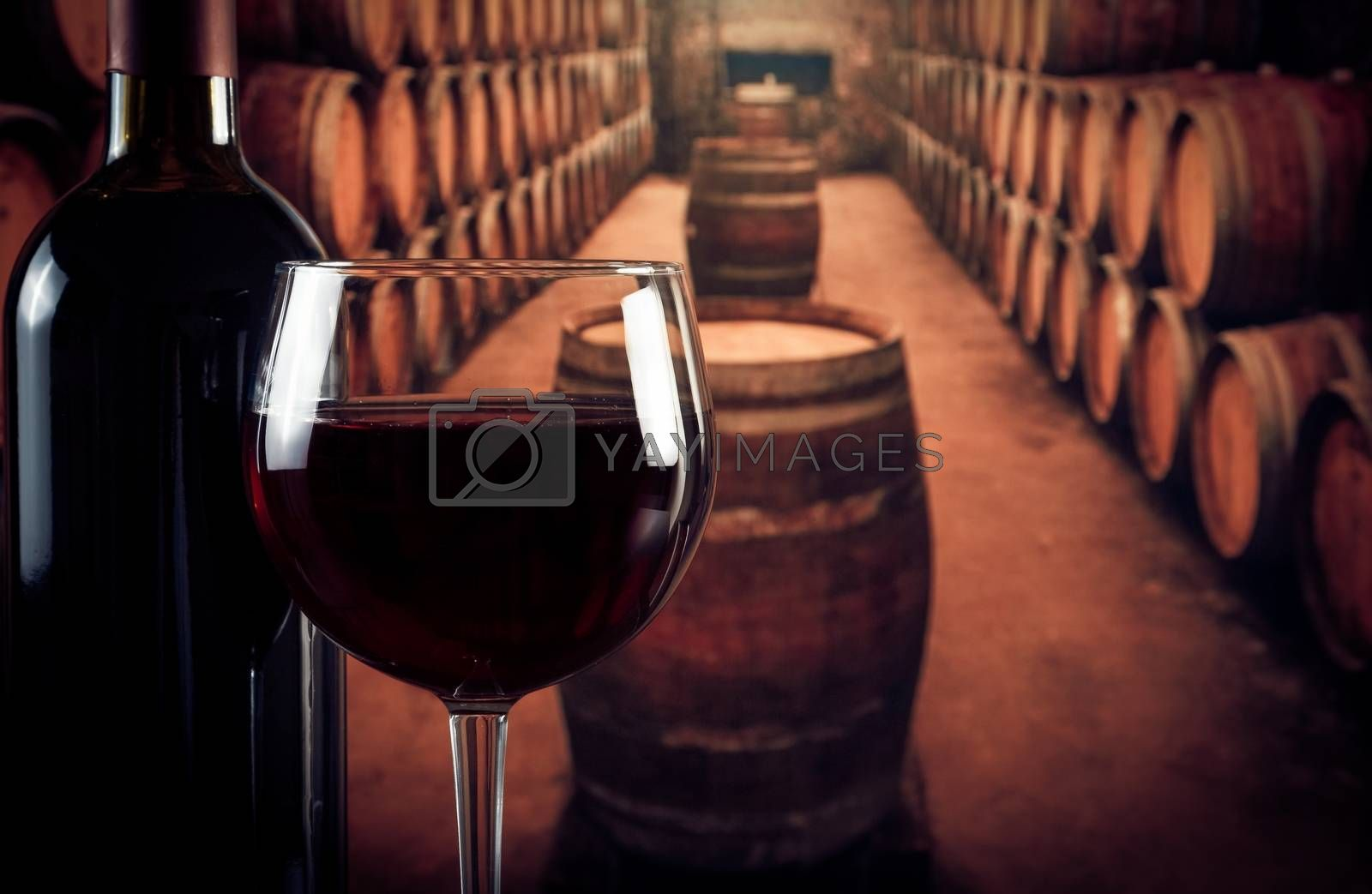wine glass near bottle in old wine cellar with space for text by donfiore