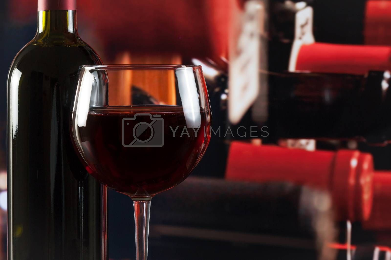 wine glass near bottle in wine cellar with space for text by donfiore