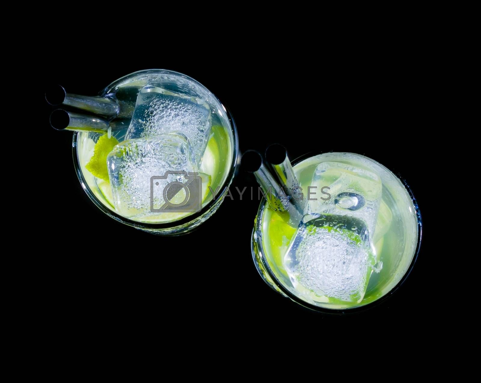 top of view of glasses with cocktail and ice with lime slice on black background by donfiore