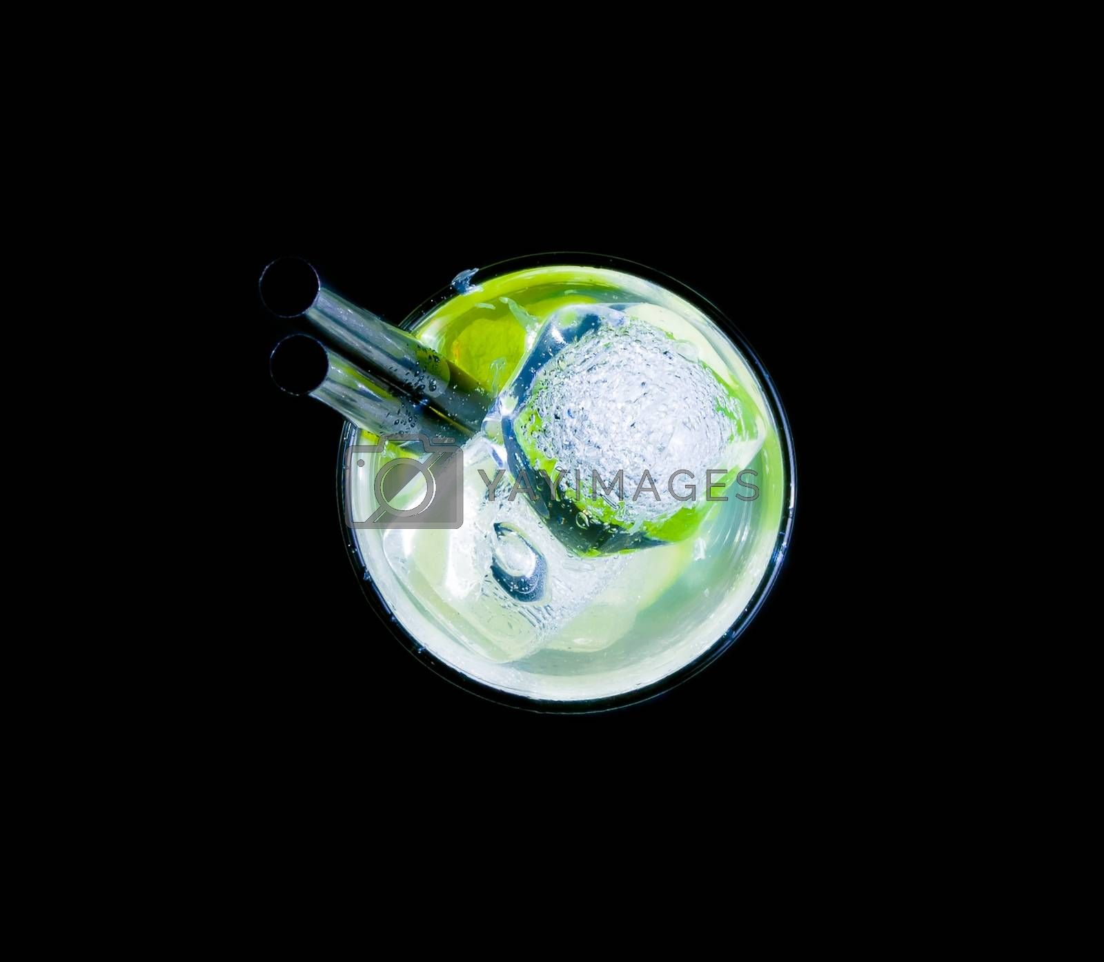 top of view of glass with cocktail and ice with lime slice on black background by donfiore