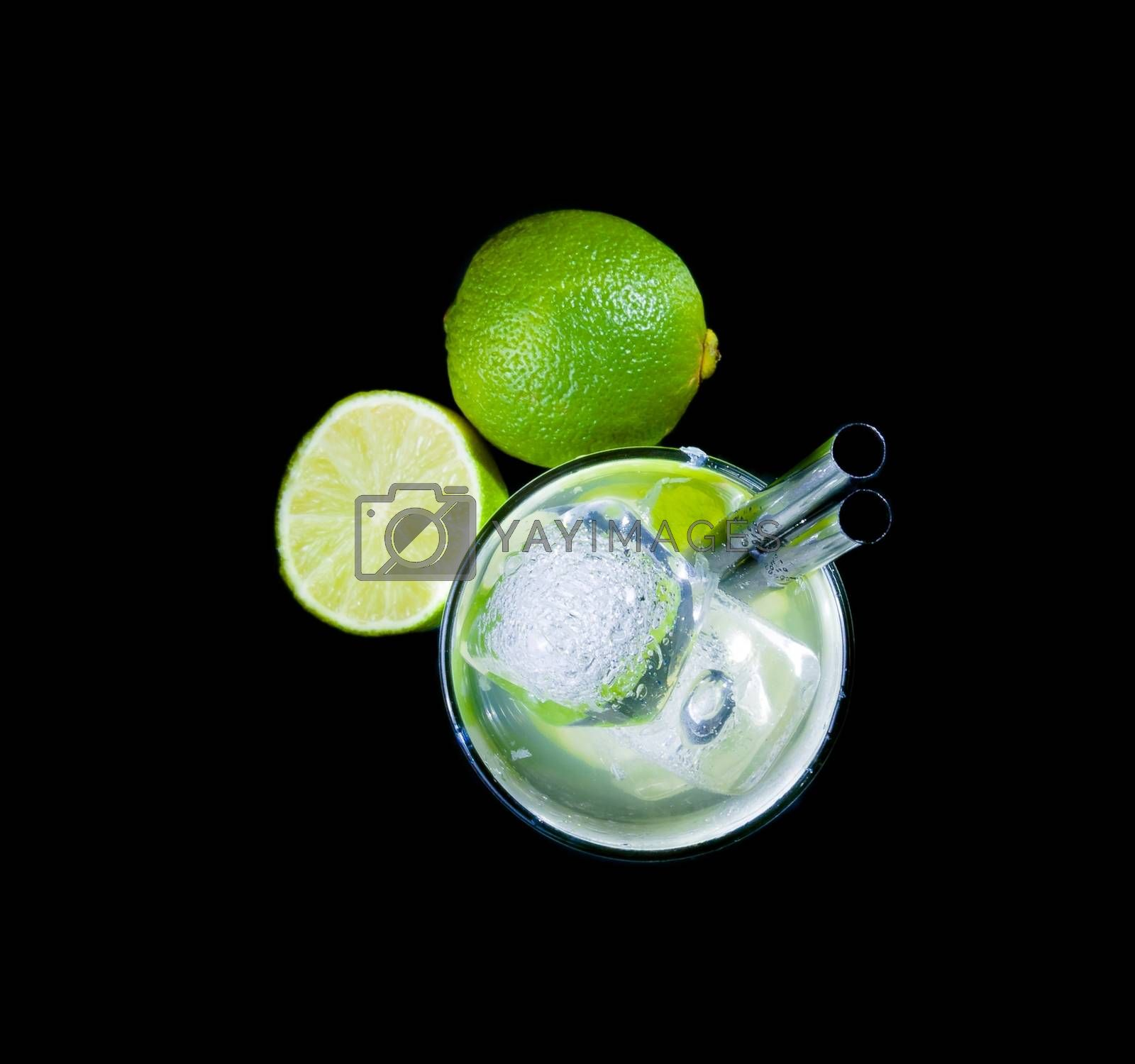 top of view of glasses with cocktail and ice near lime on black background by donfiore