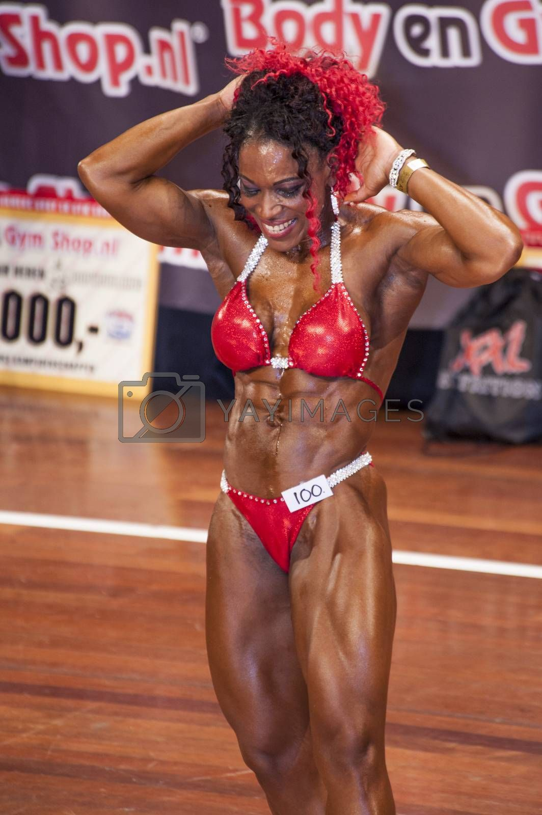 Female bodybuilder in abdominals and thighs pose and red bikini by yellowpaul