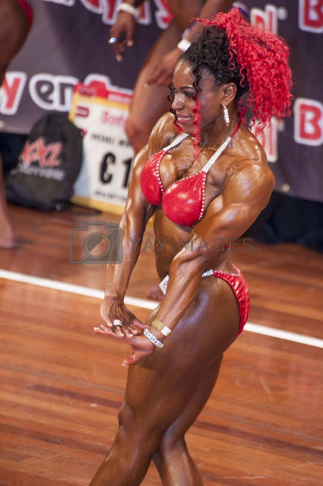 Female bodybuilder in triceps pose and red bikini by yellowpaul