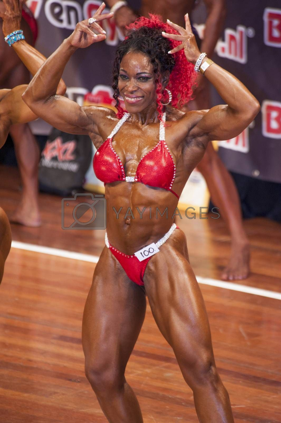 Female bodybuilder in double biceps pose and red bikini by yellowpaul