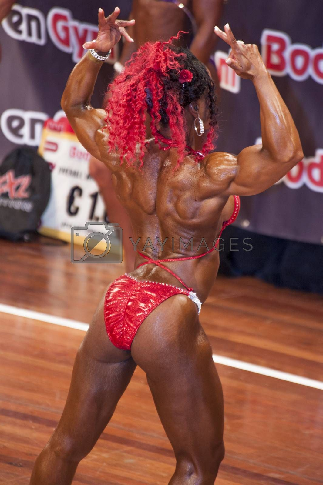 Female bodybuilder in back double biceps pose and red bikini by yellowpaul