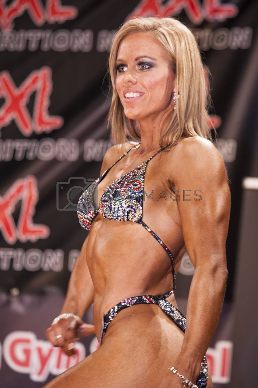 Female bodyfitness contestant shows het best front pose on stage by yellowpaul