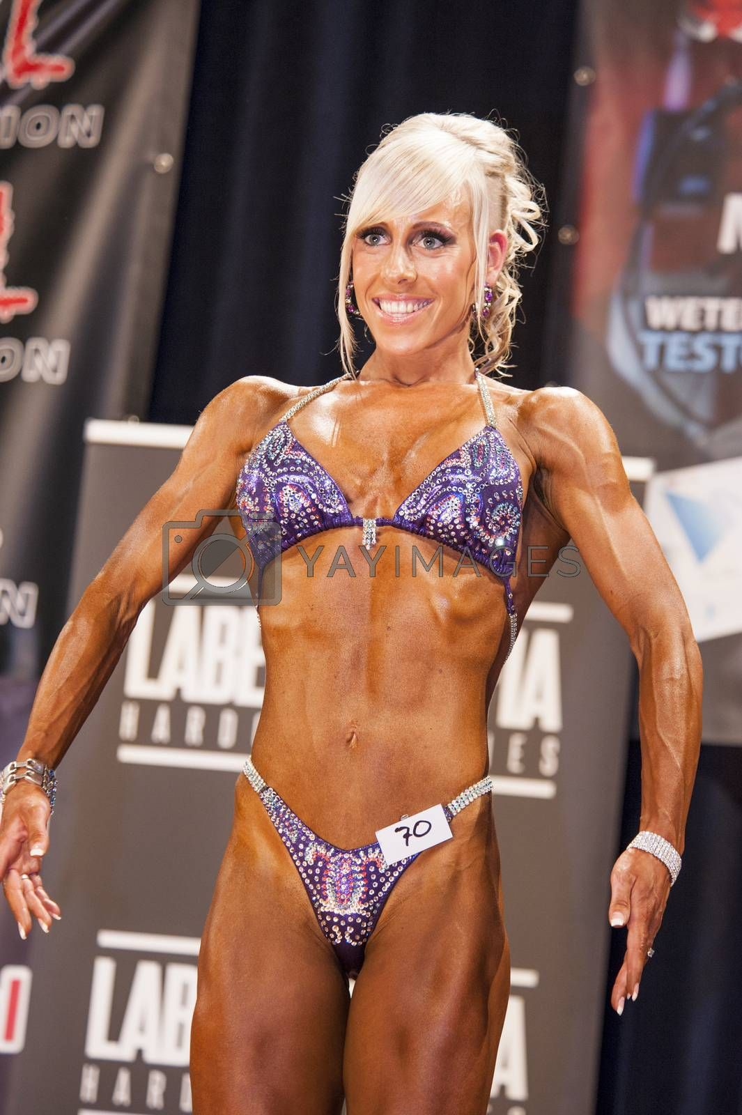 Female bodybuilder shows her best front pose on stage by yellowpaul
