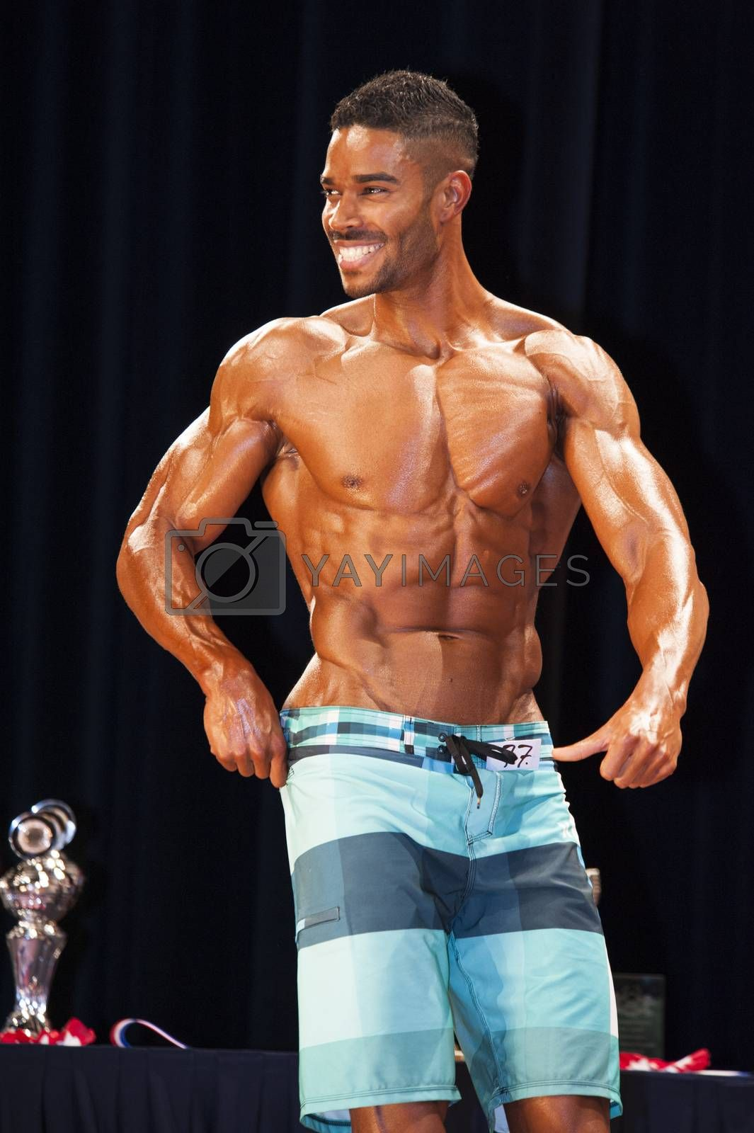 Fitness contestant shows his best chest pose on stage by yellowpaul