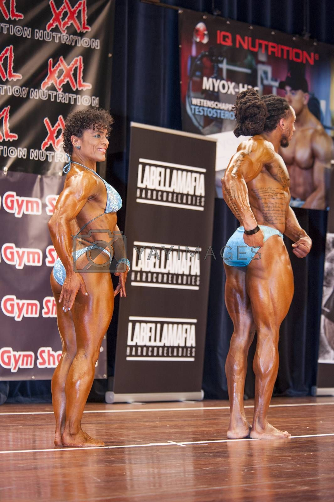 bodybuilding duo in relaxed side pose on stage by yellowpaul