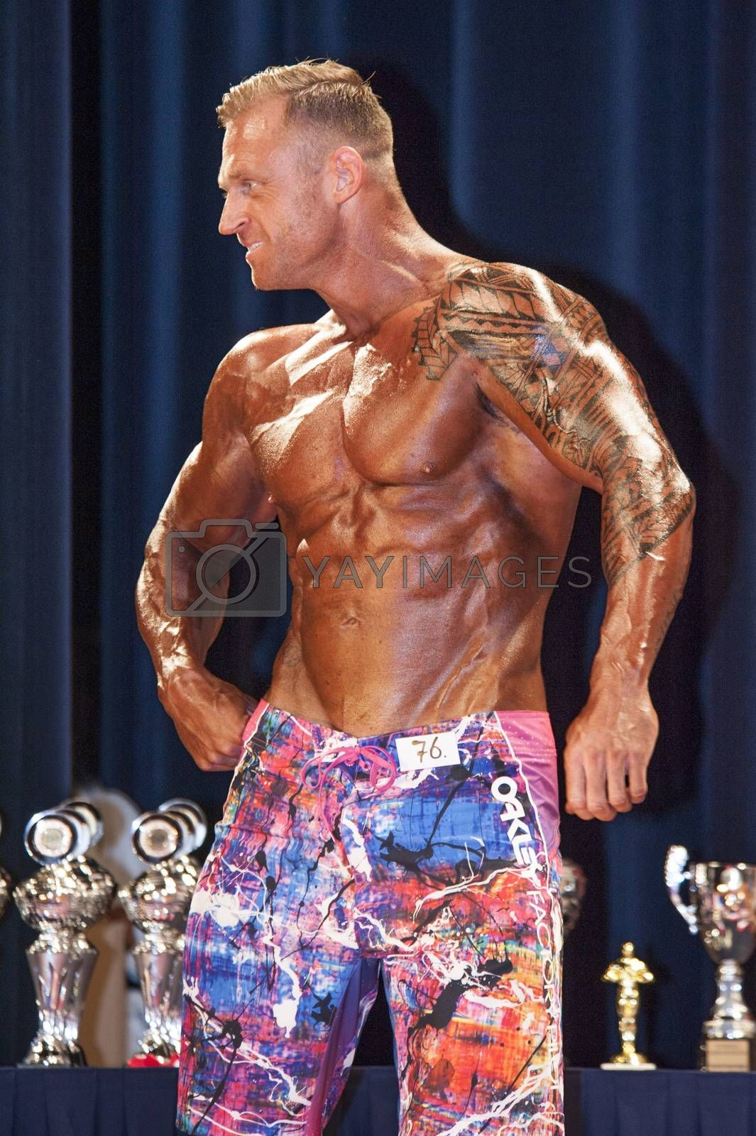Male bodybuilder shows his best chest pose on stage by yellowpaul