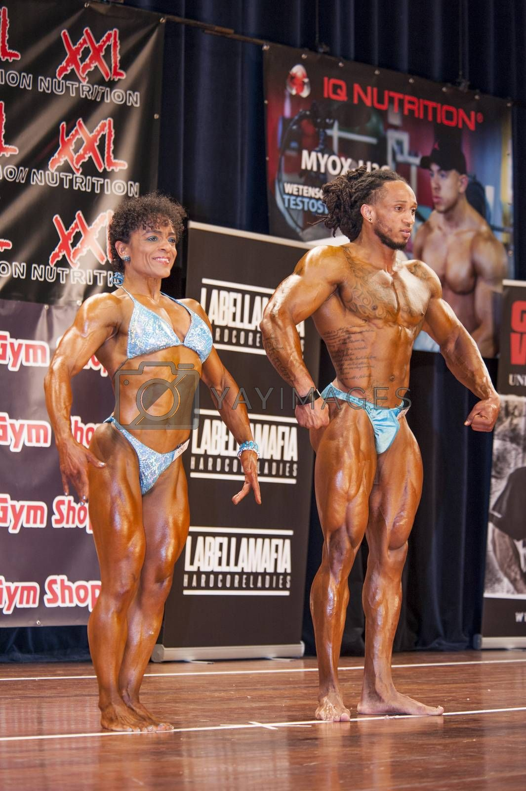 bodybuilding duo in relaxed front pose on stage by yellowpaul