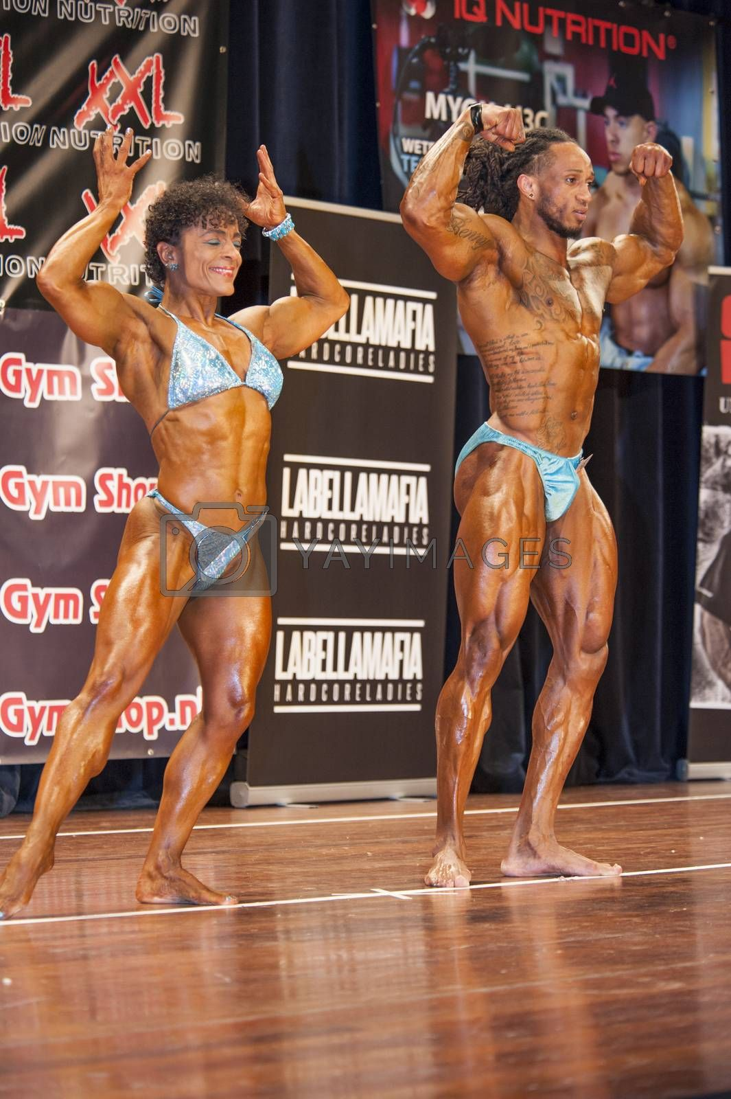 bodybuilding duo in front double biceps pose on stage by yellowpaul